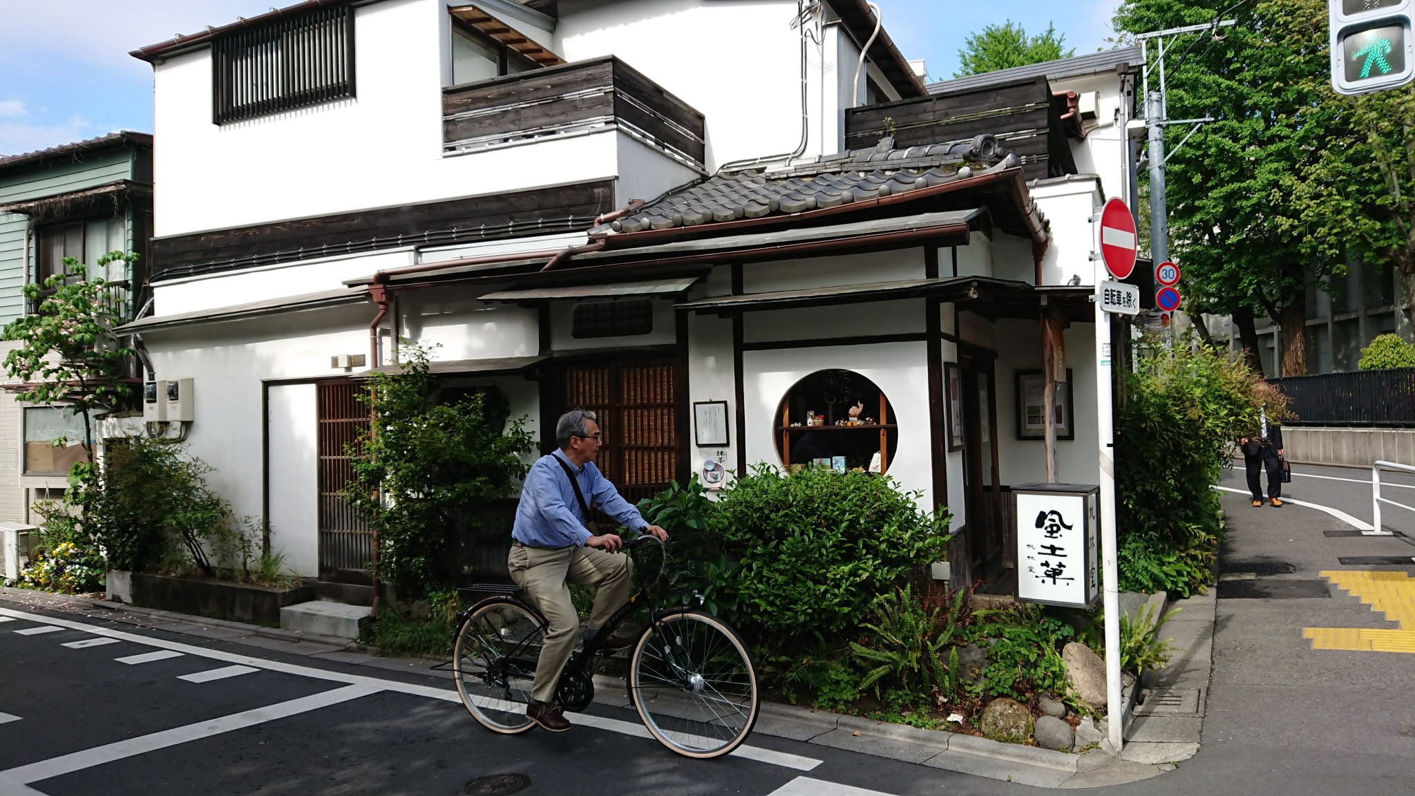 A middle-aged man in shirt and chinos rides his bike through a quiet old neighbourhood
