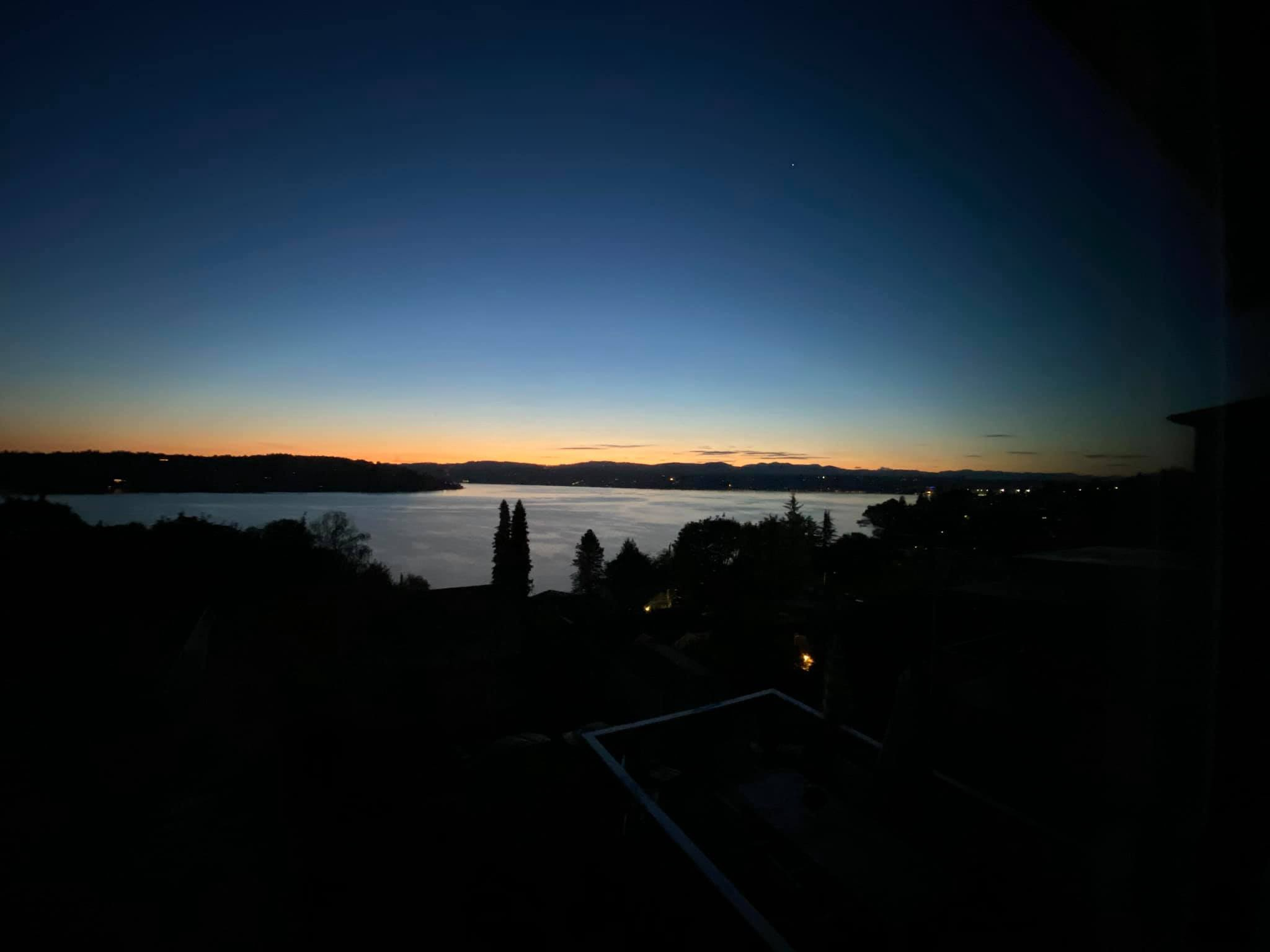 A sunrise over Lake Washington with a band of sherbet orange below rising bands of blue growing darker until almost black.