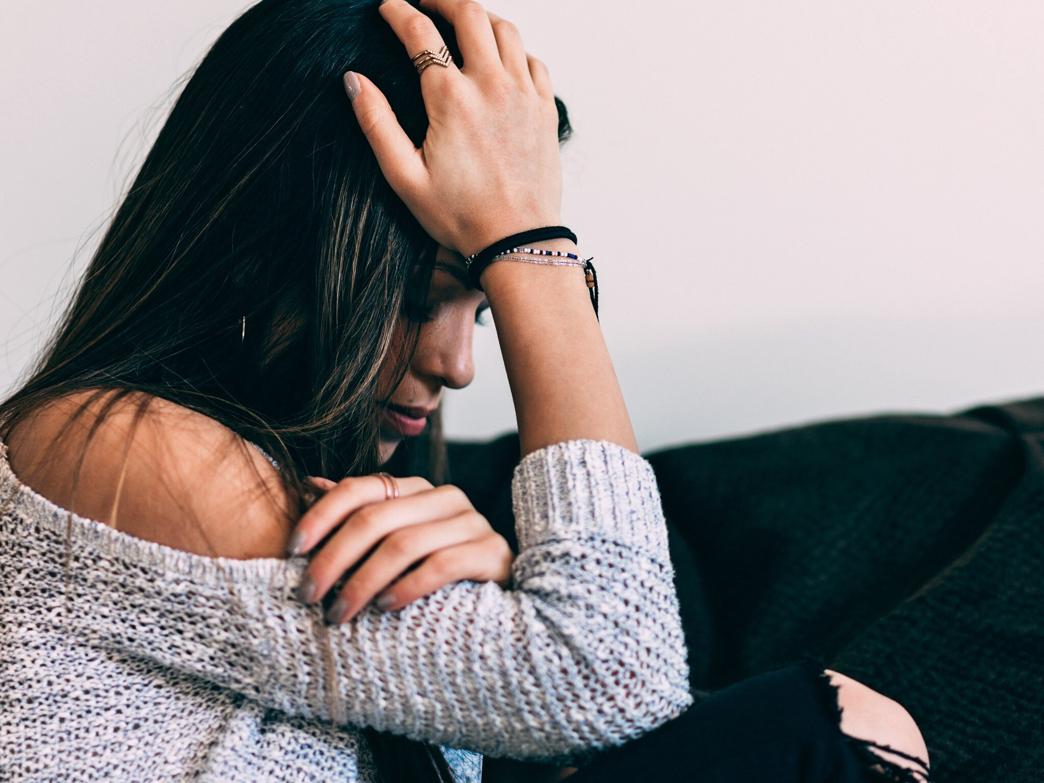 A sad woman with dark hair holds her head in her hands on a couch.