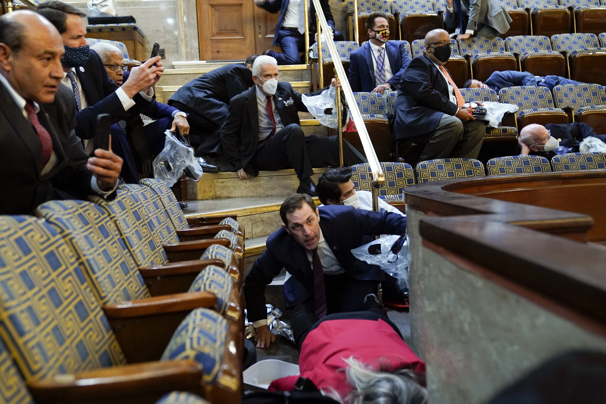 People shelter in the House gallery as protesters try to break into the House Chamber at the US Capitol on Wednesday, Jan. 6, 2021, in Washington. (AP Photo/Andrew Harnik)