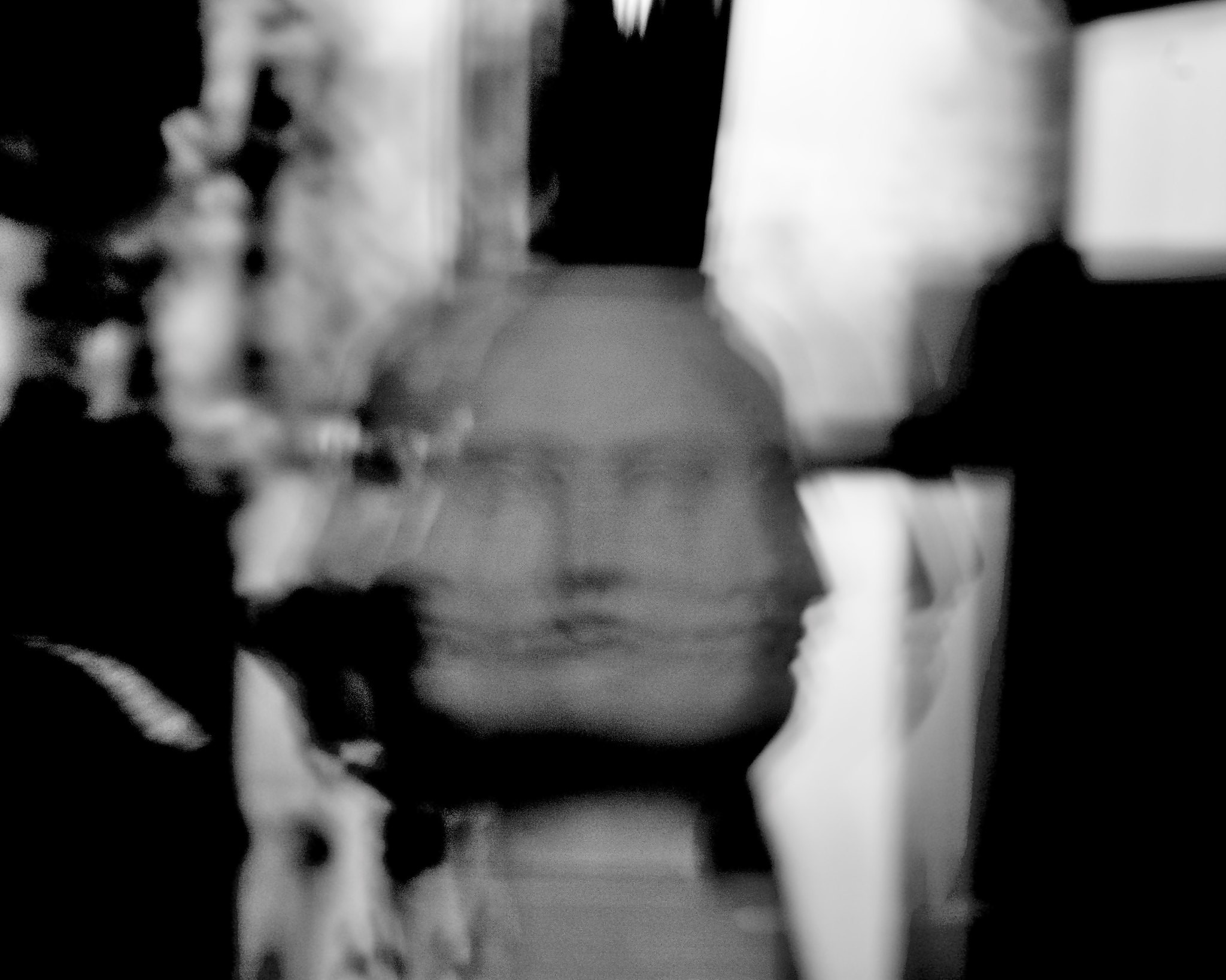Black and white superimposed image of a sculpture of a face.