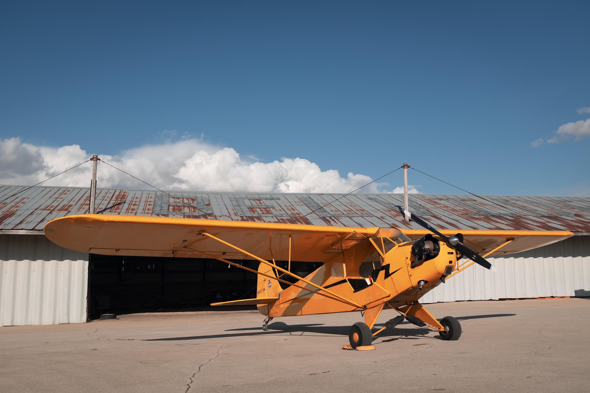 Yellow Piper J-3 Cub (N6673H) parked outside hangar at Poplar Grove Airport (C77) on sunny day