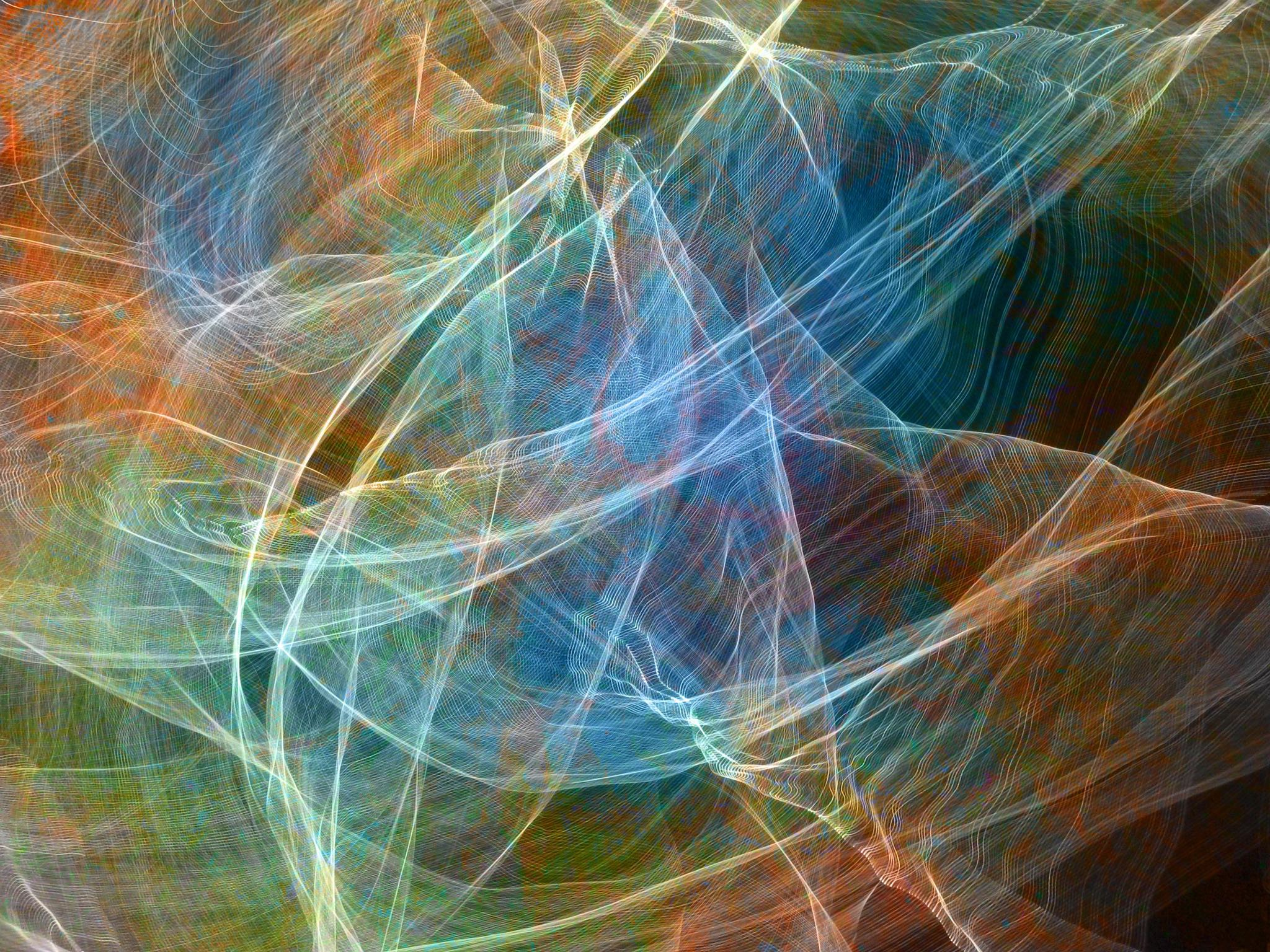 This abstract photograph shows swirls of floating colored light that look like translucent fabric or a distant nebula.