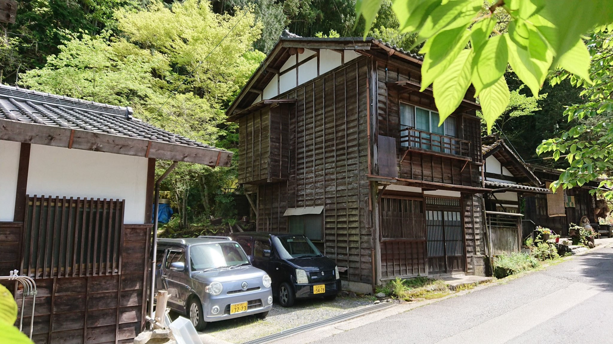 Two little cars sit in the drive of a beautiful dark-timber house on a leafy slope