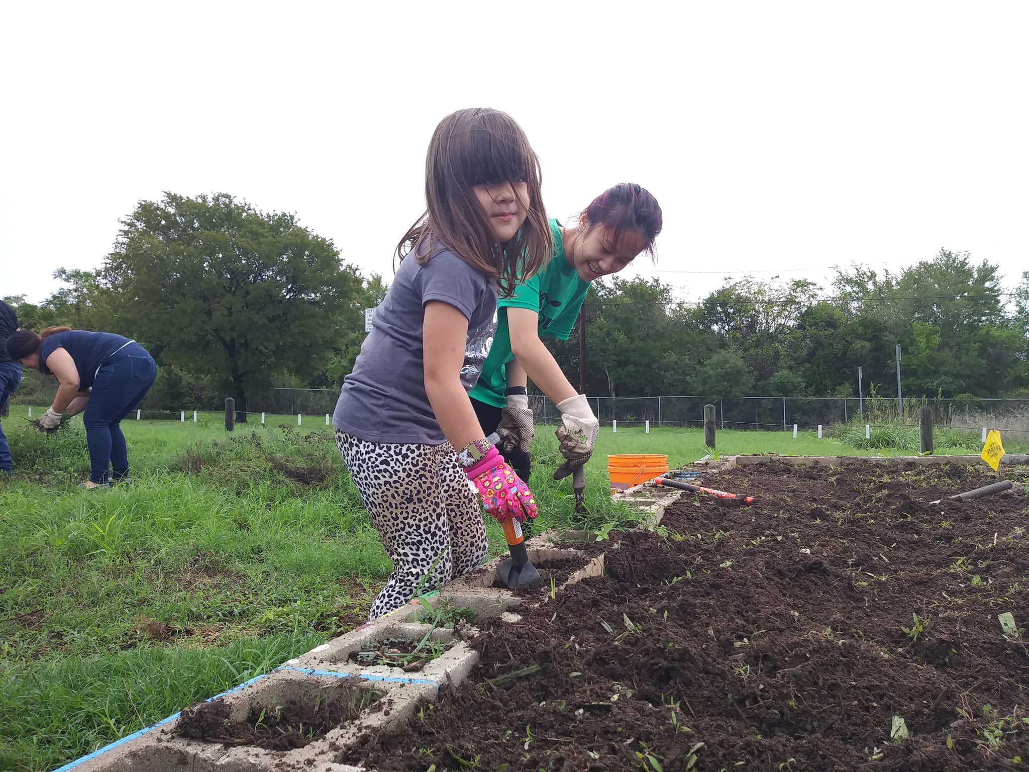 Two little girls dig in a school garden at Pleasant Hill Elementary in South Austin.