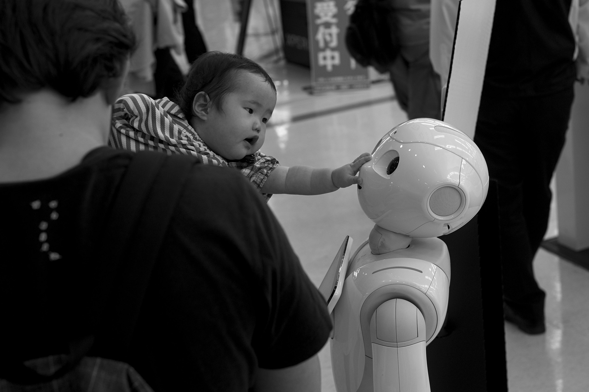 a baby interacting with Pepper the robot, taken from https://www.flickr.com/photos/jeena/37017614286/