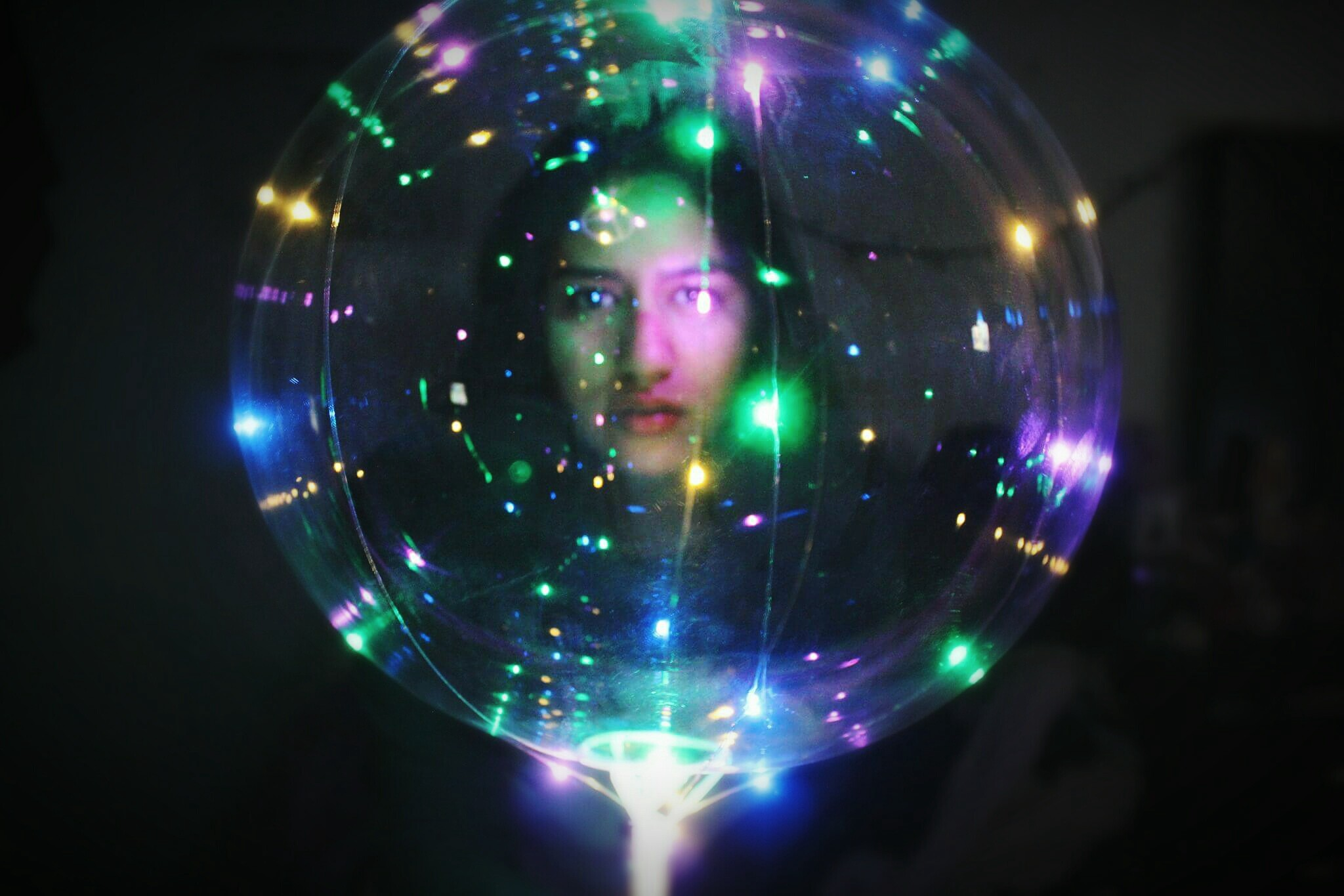A photo of a woman with an illuminated transparent ball in a dark room.