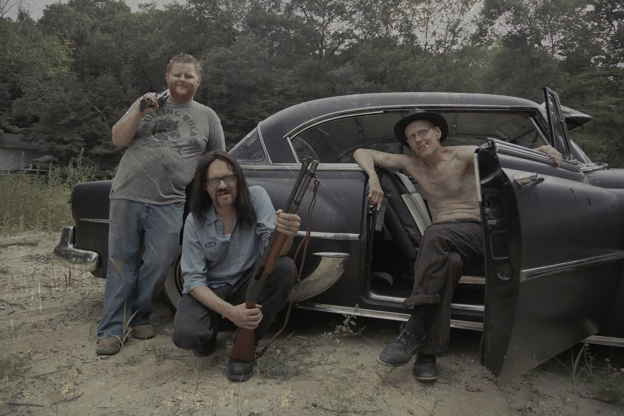 Photo of three men with guns lounging by the side of a car.
