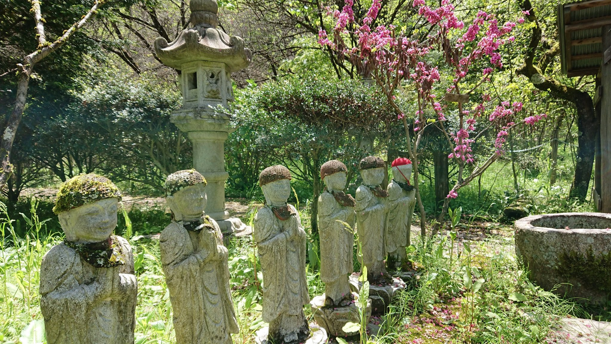 A row of stone statues at a shrine, wearing knitted hats