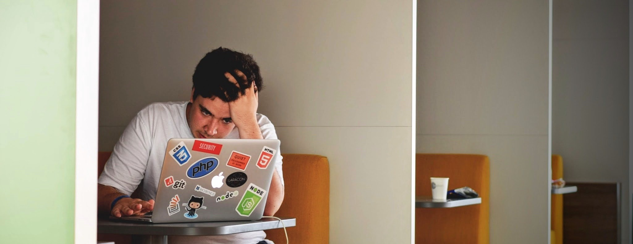 Man with his head in his hand, staring at a laptop