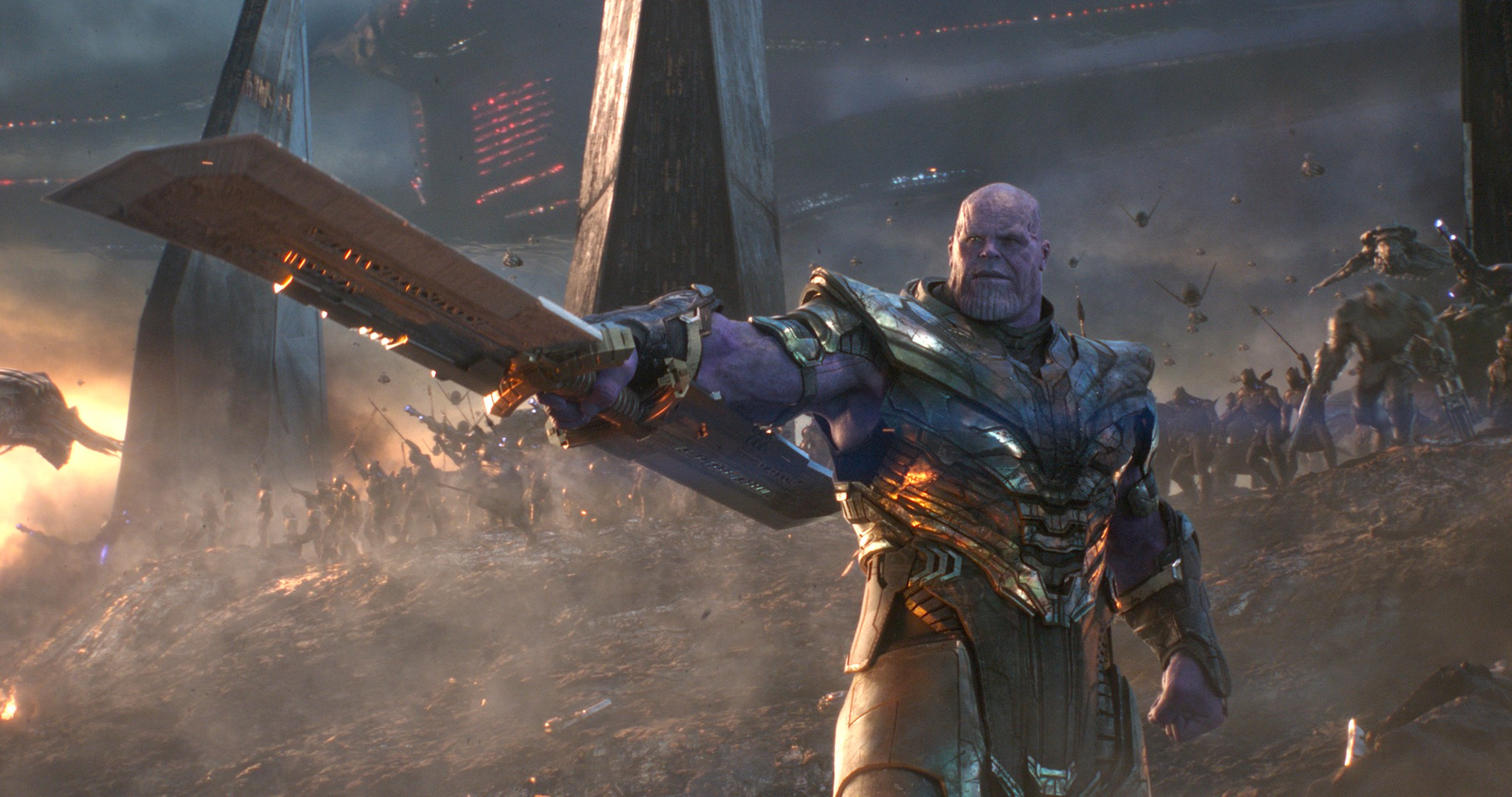 Thanos brandishing a weapon on the battlefield with a huge spaceship in the background.