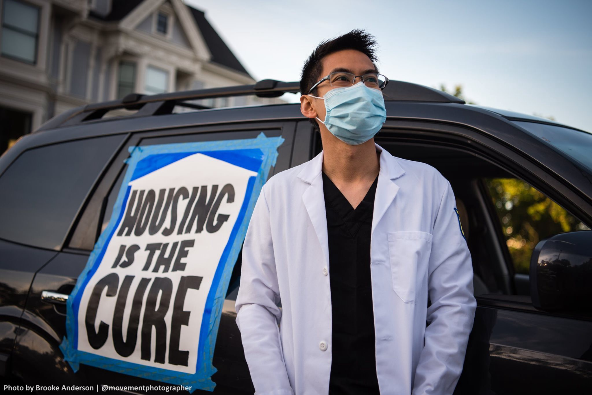 "A person in a medical mask and white doctor's coat stands in front of a vehicle with a sign that reads ""HOUSING IS THE CURE"""