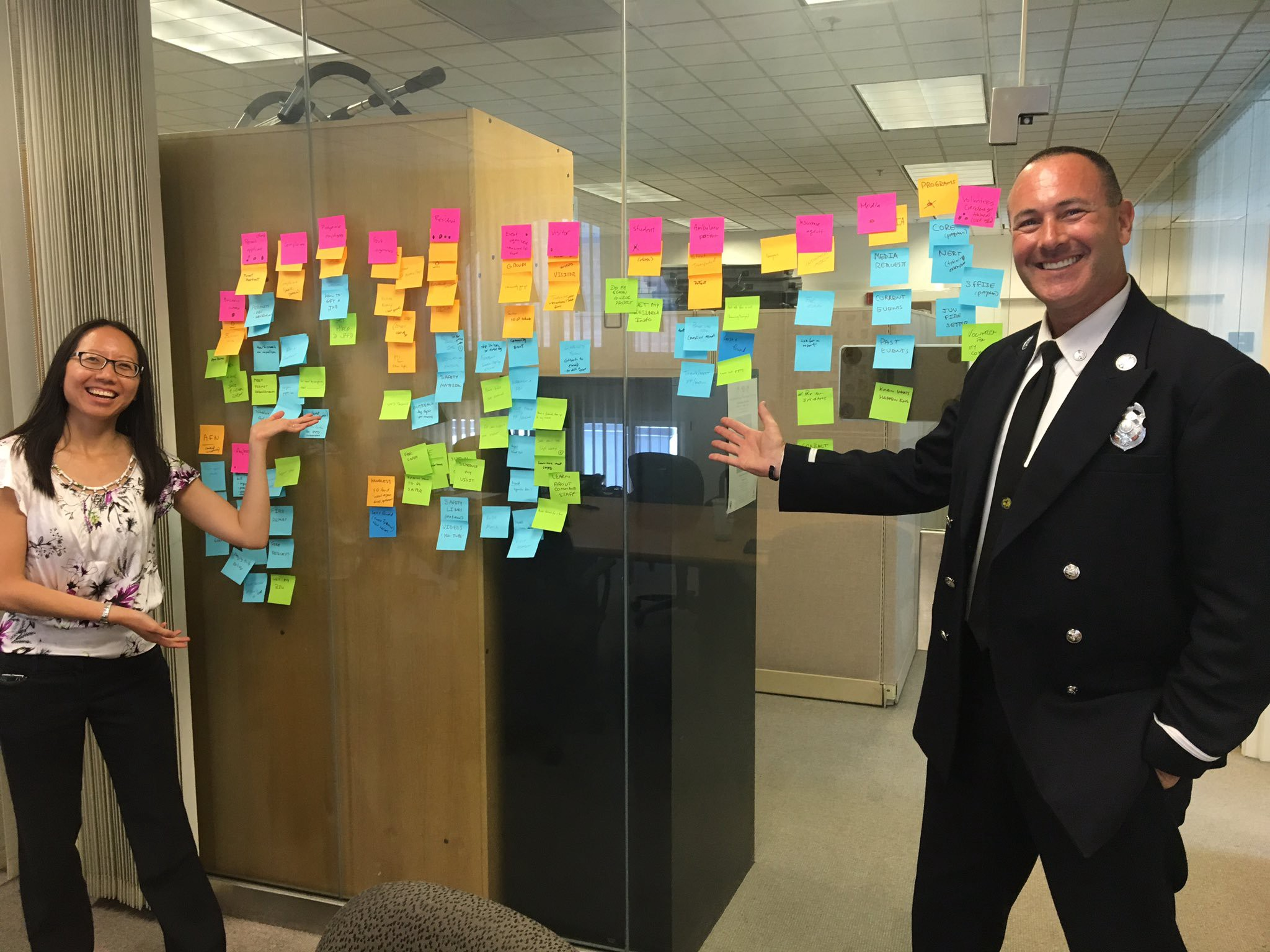 A content designer and Public Information Officer pose with a meeting room window covered in Post-Its after a workshop.