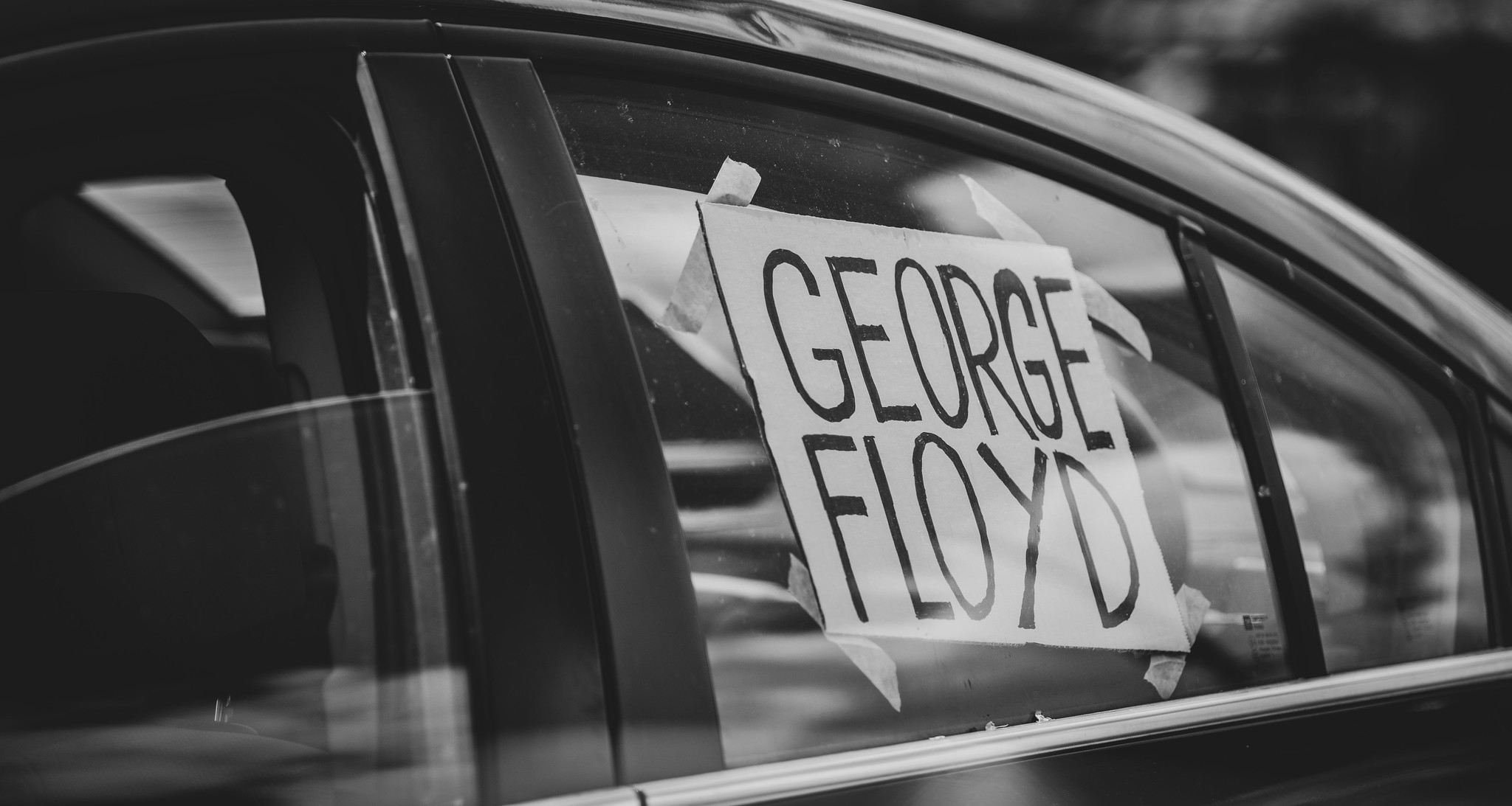 "Car window with ""George Ford"" sign taped to it."