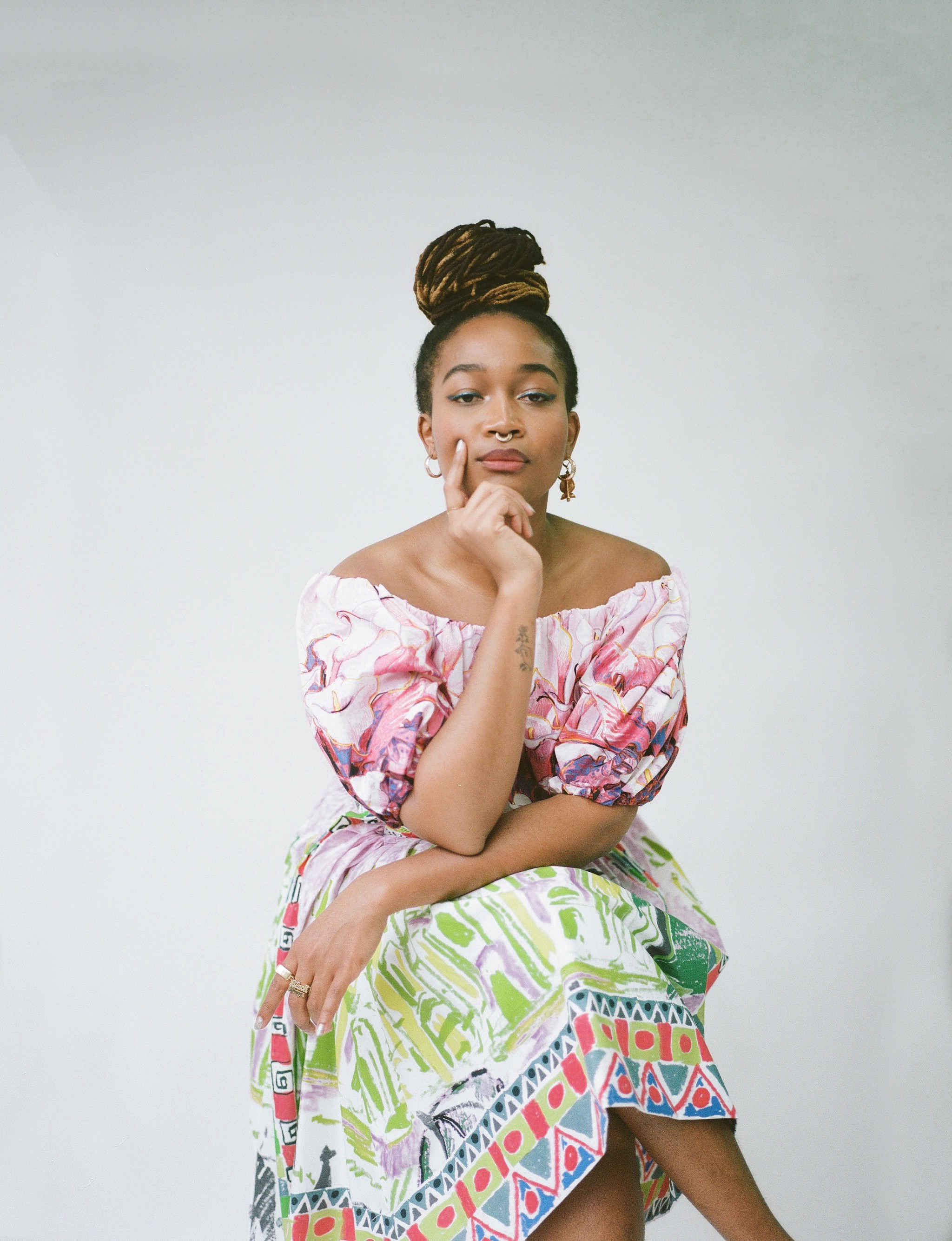 Kimberly Drew poses seated in a floral dress.