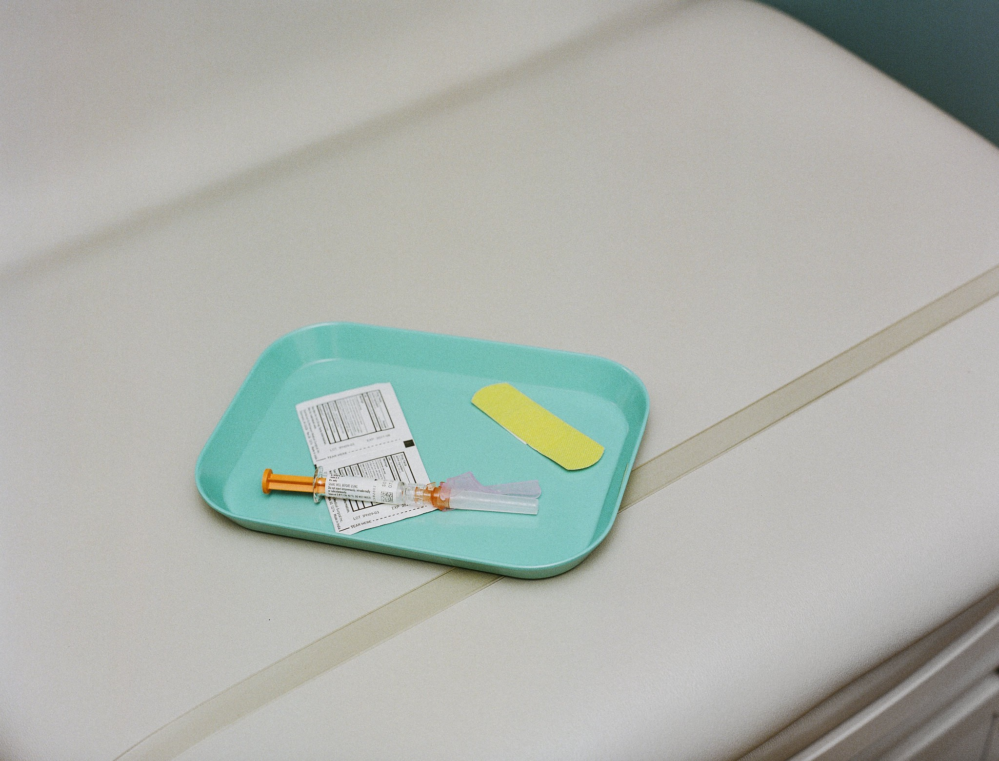 A tray with a bandaid and shot.