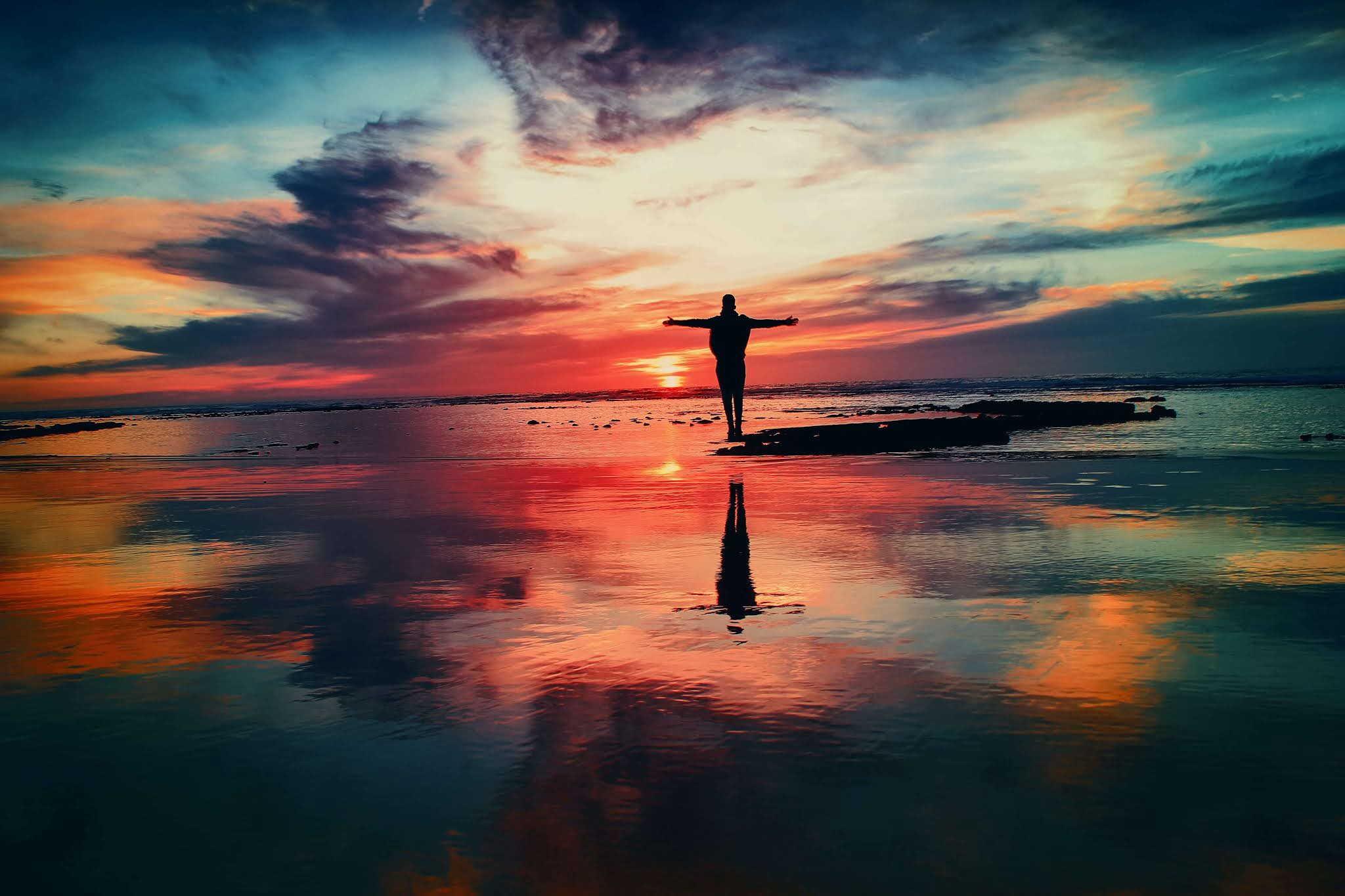 Man with open arms forming a cross with sky reflected in the water beneath him and sunsetting with way too much different colors other than orange