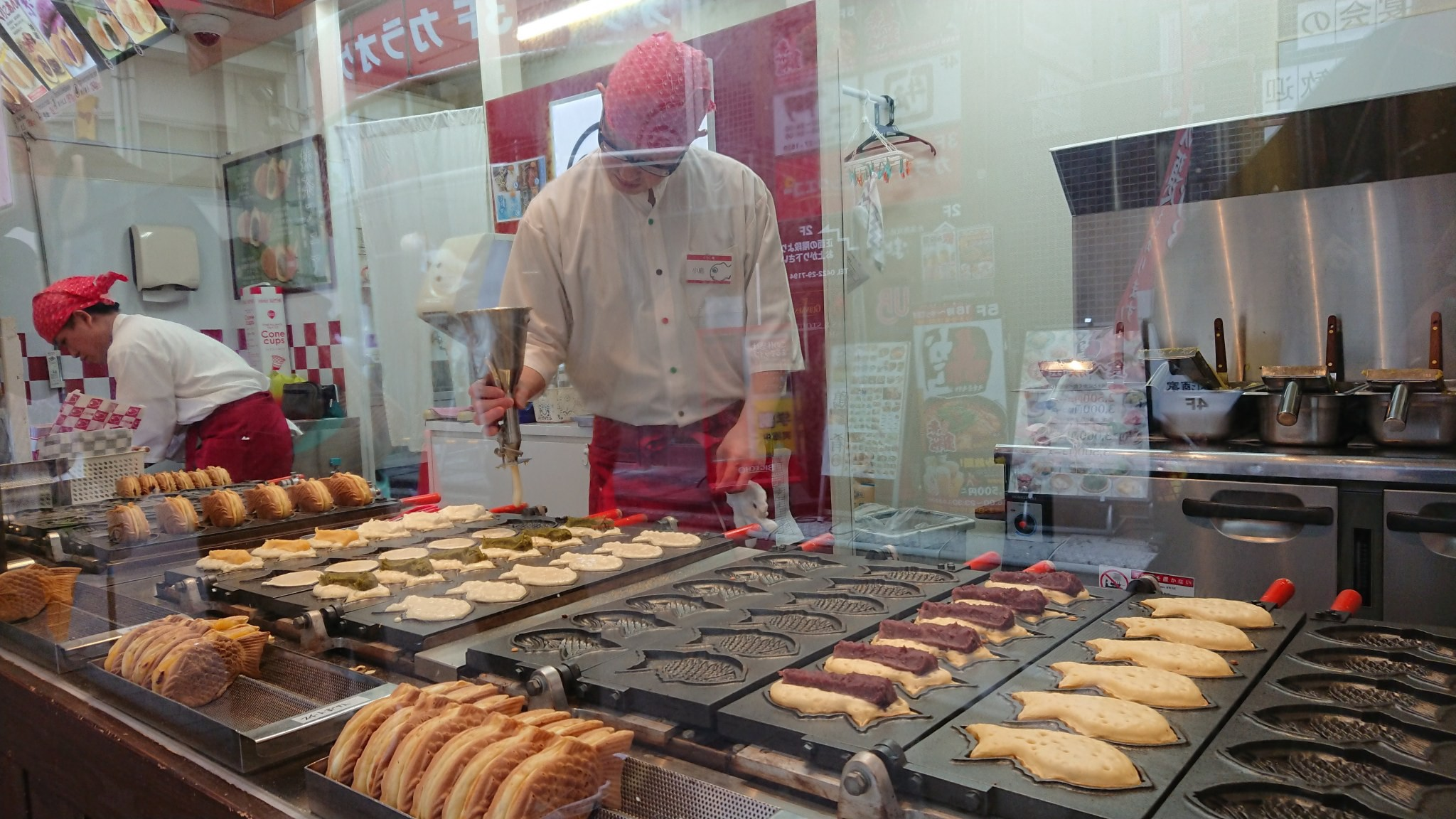 Through a glass screen, a taiyaki-maker adds some finishing touches to a large tray of the stuff.