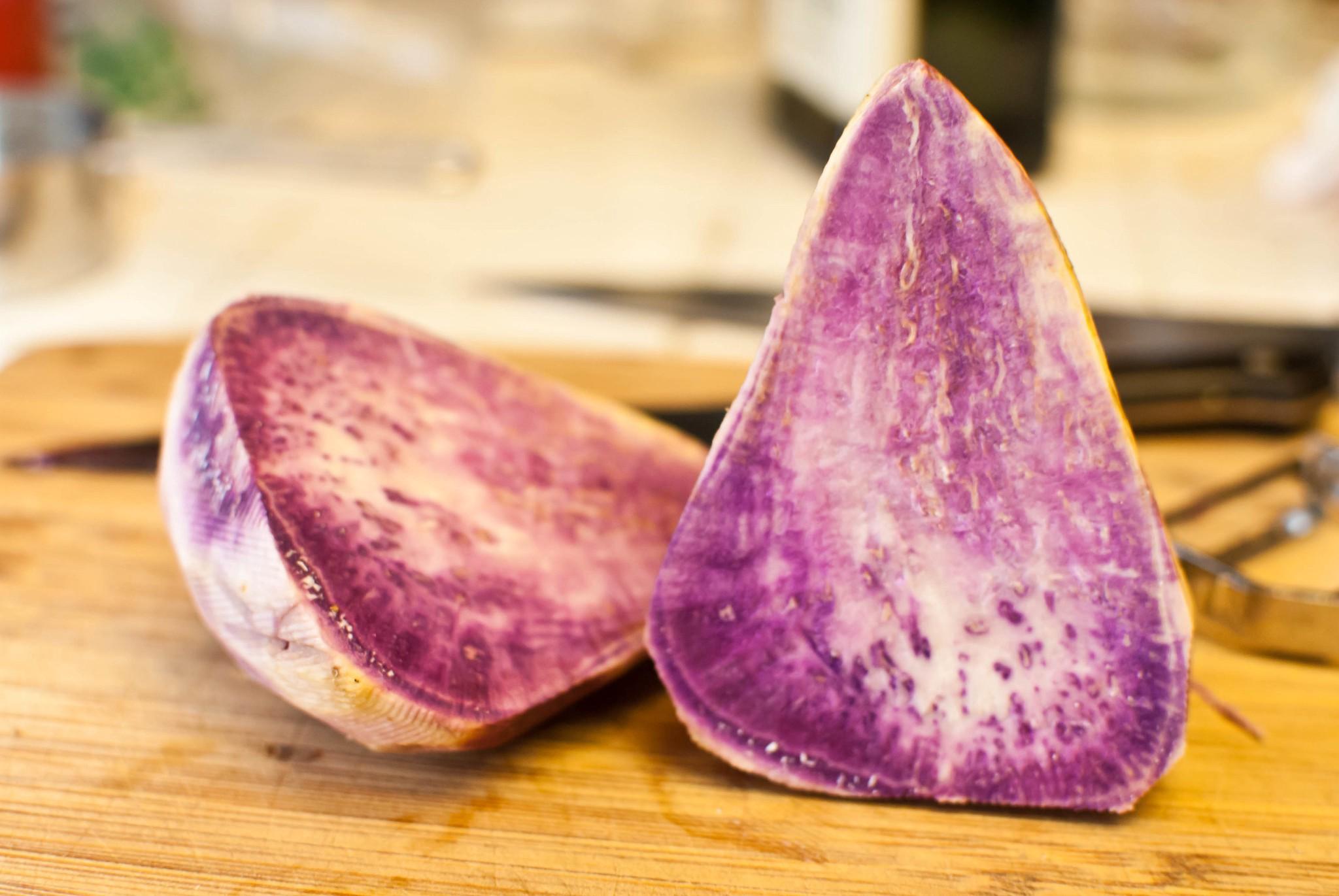 Two halves of a pear-shaped Okinawa sweet potato on a timber board with the white-streaked purple flesh exposed.