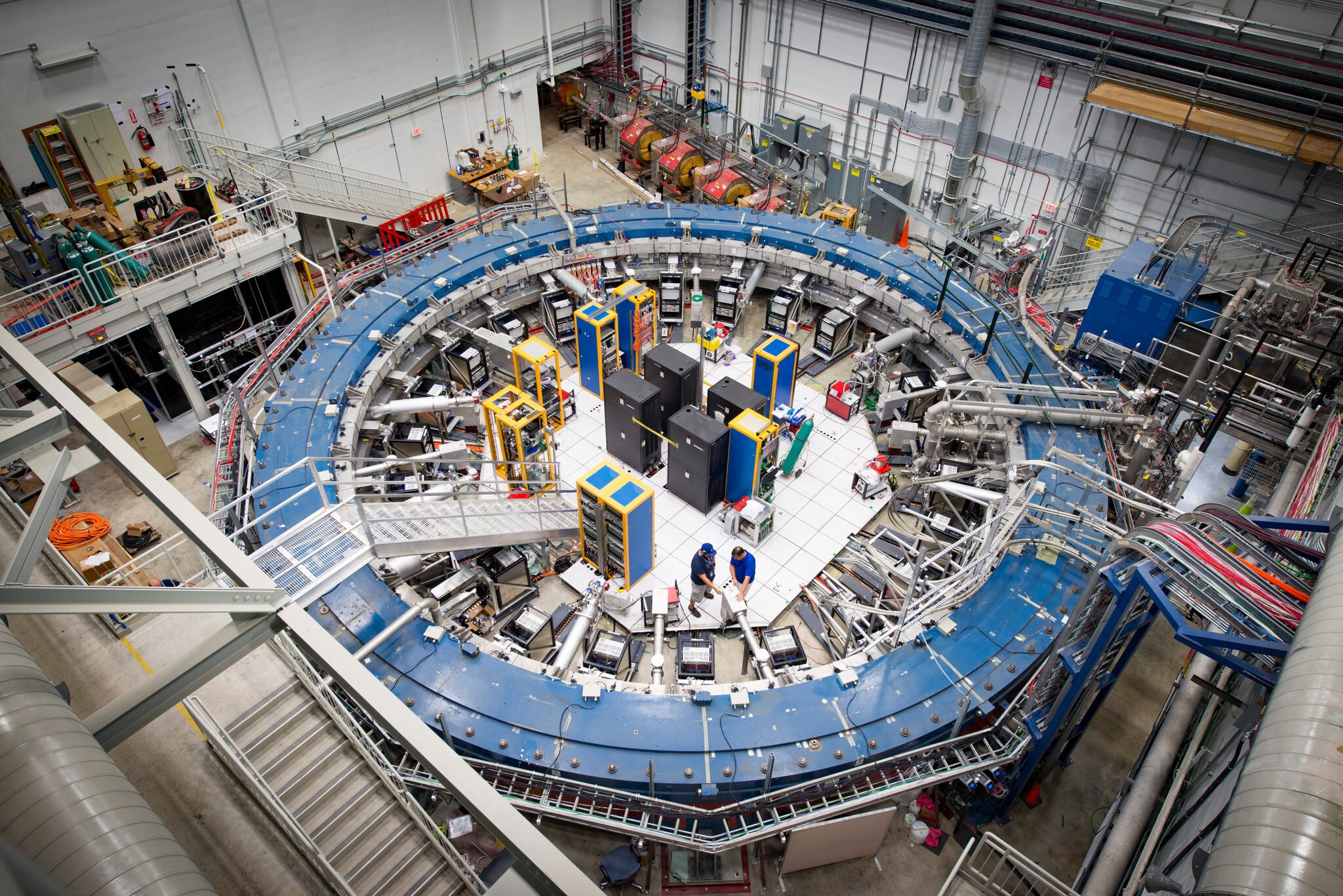 This is a picture of the Muon g-2 ring at The Fermi National Accelerator Laboratory in Batavia, Ill. A wide open science lab showing a magnetic field blue ring in an aerial shot. Two scientists are on the floor experimenting with magnetic ring researching this muon particle.