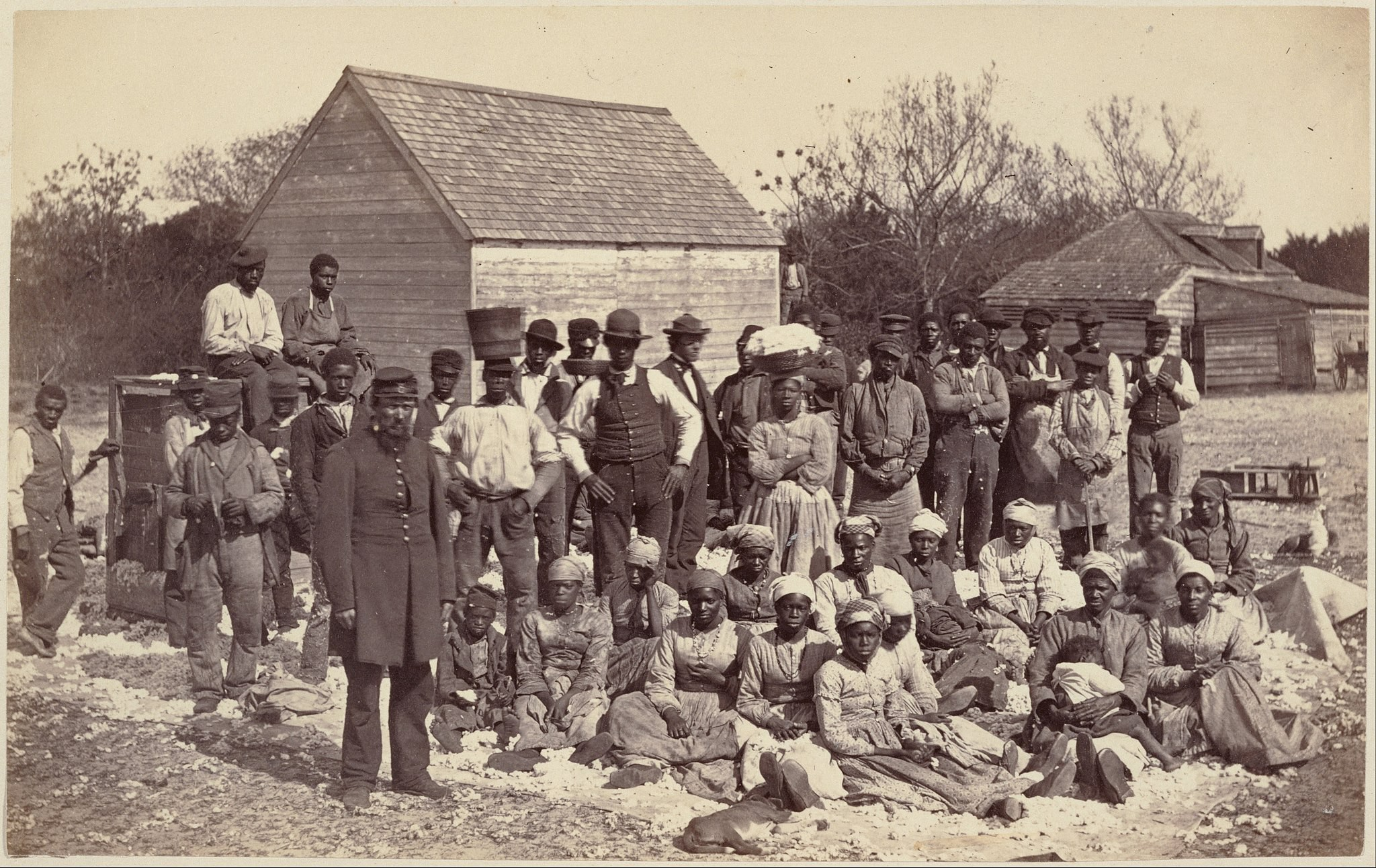 Dozens of slaves owned by an American military general posed outside a wooden house