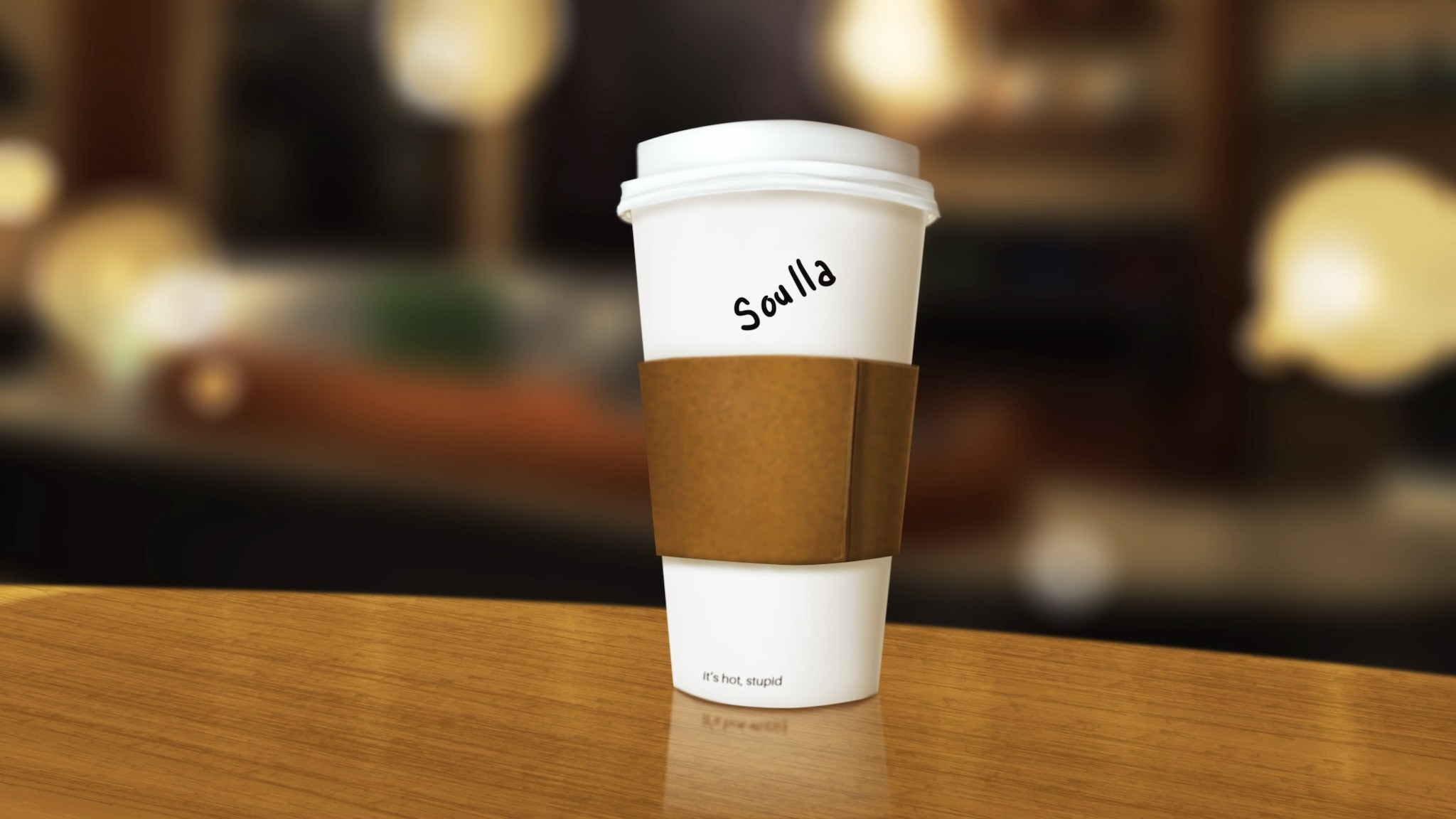 """A standard Starbucks-style coffee cup to-go with a thin, insufficient-seeming band of brown cardboard wrapped around the white cup to protect the buyer's hands. On the cup itself, someone wrote with black sharpie """"Soulla"""". Near the very bottom of the cup are some printed letters: """"it's hot, stupid""""; truly groanworthy."""