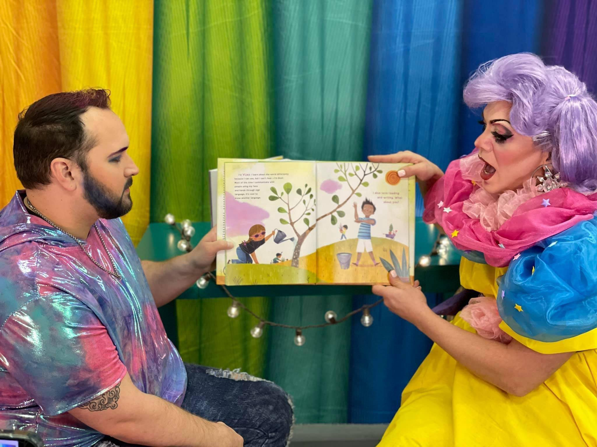 Two Drag Queen Story Time presenters are holding up a children's book in front of a rainbow background as they read the story aloud