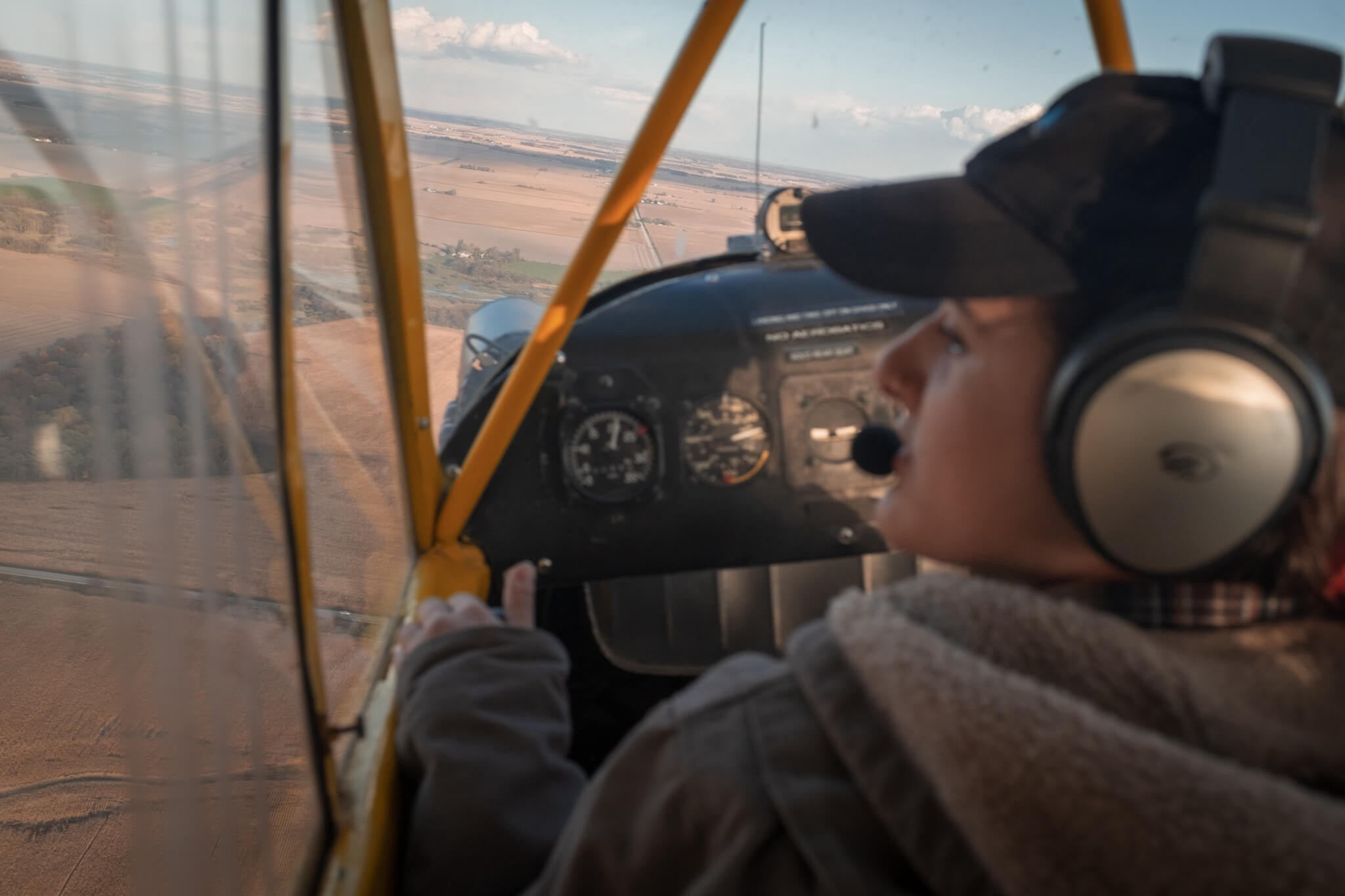 Piper J-3 Cub (N6673H) cockpit with CFI Lana Tollas scanning for traffic on base leg while on downwind leg of traffic pattern