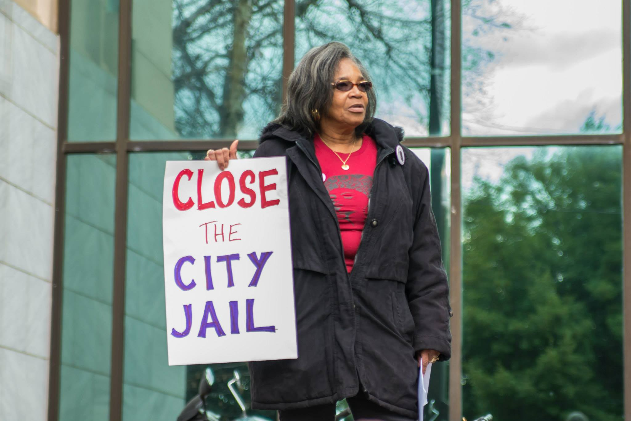 """Black woman in a red Women on the Rise shirt and sunglasses with black long jacket and sign that reads """"Close The City Jail"""""""