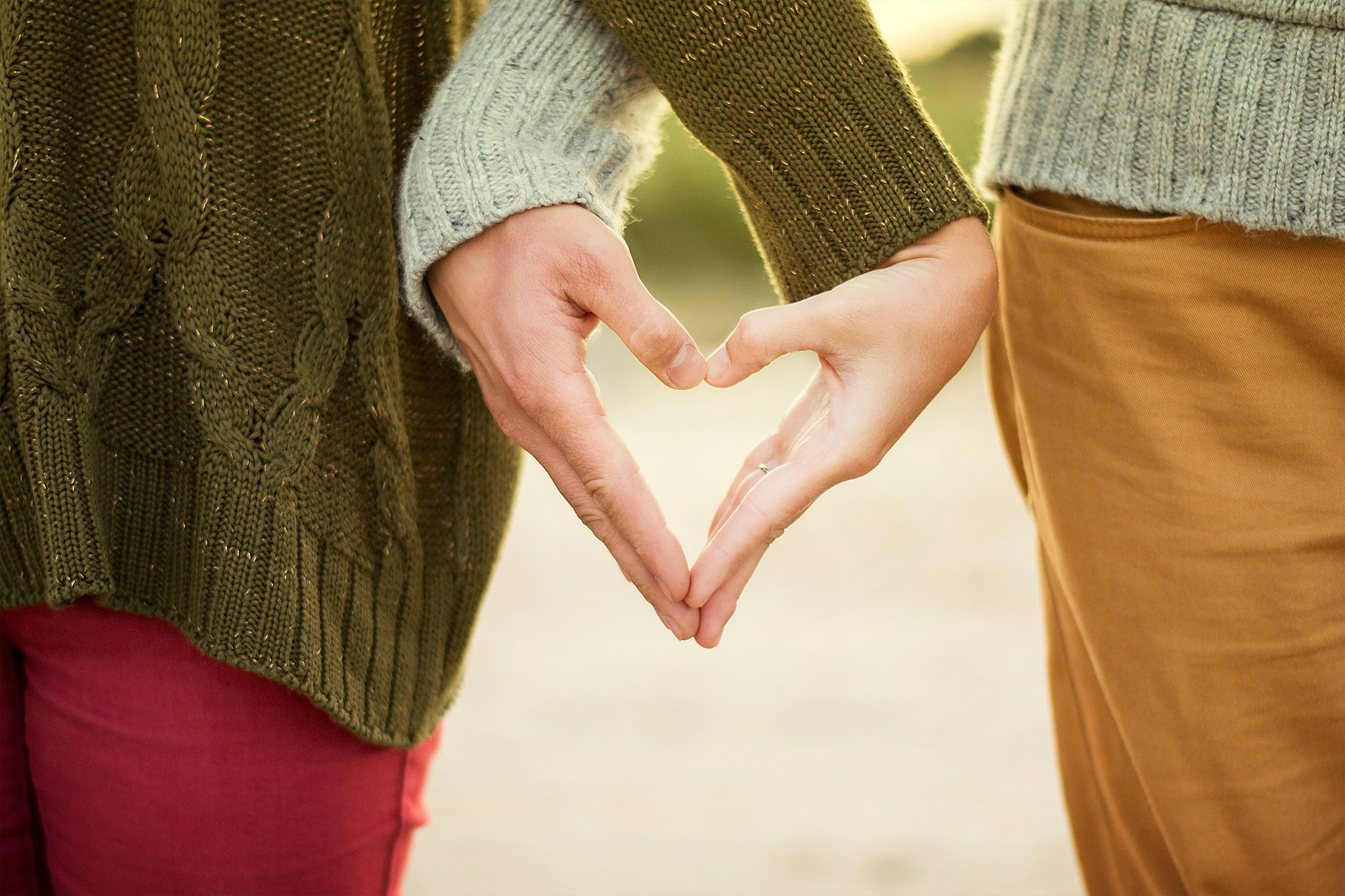 Two people forming a heart shape with their hands