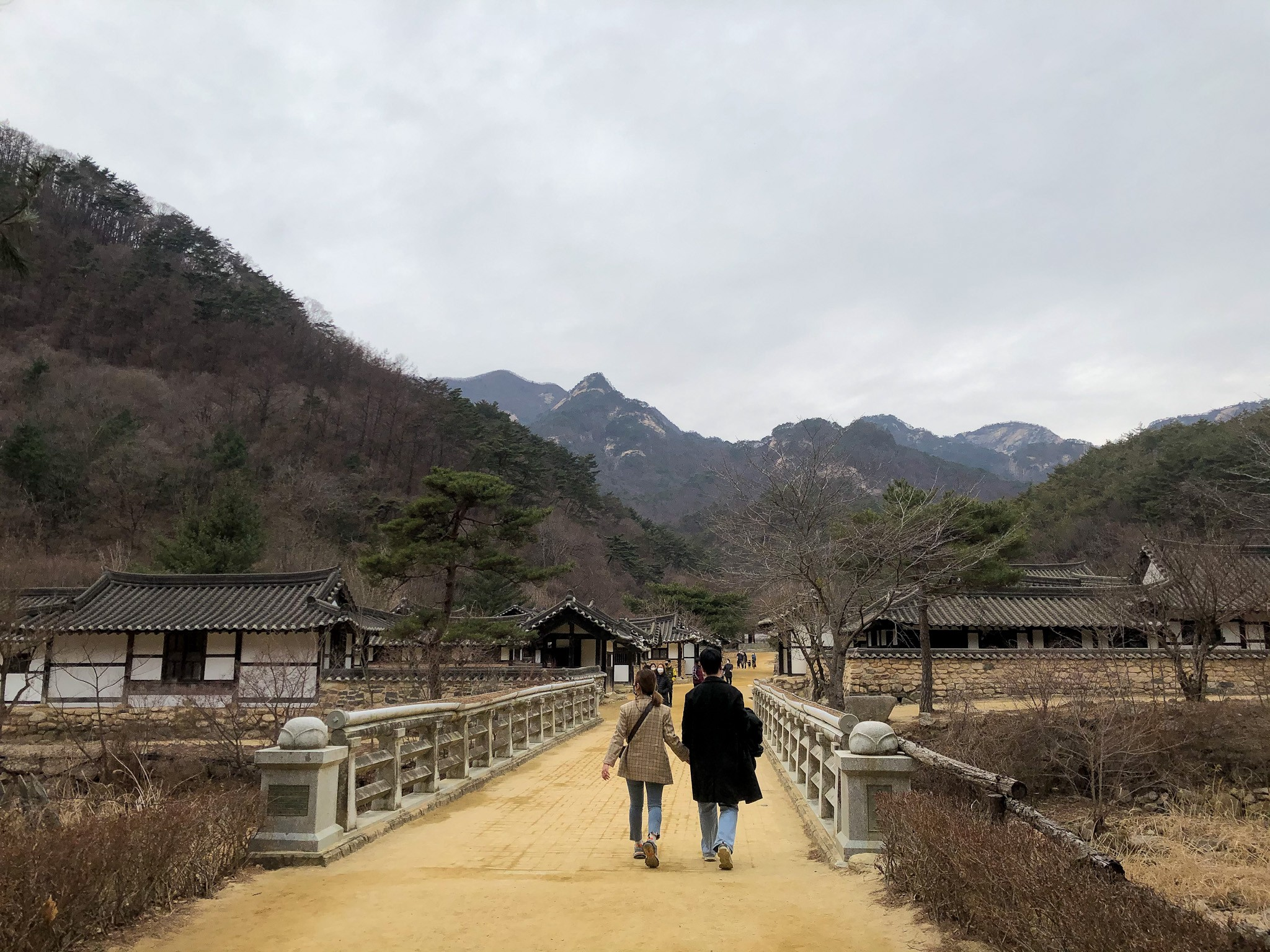 Mungyeong Saejae stone bridge that leads hikers through a traditional Korean village with the mountains of Korea in the distance.