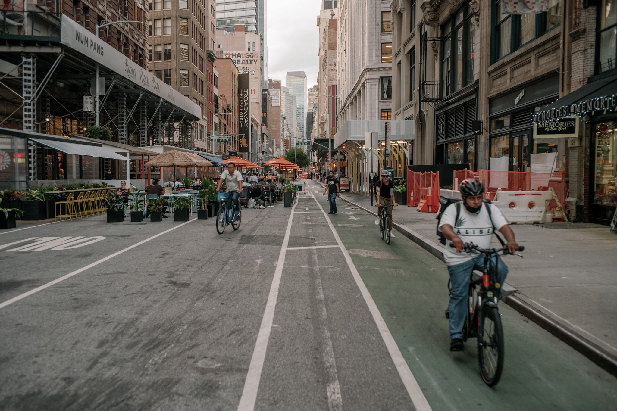 People bike down a green bike lane in Midtown NYC, while people sit in the car lane, dining at open-air restaurants.