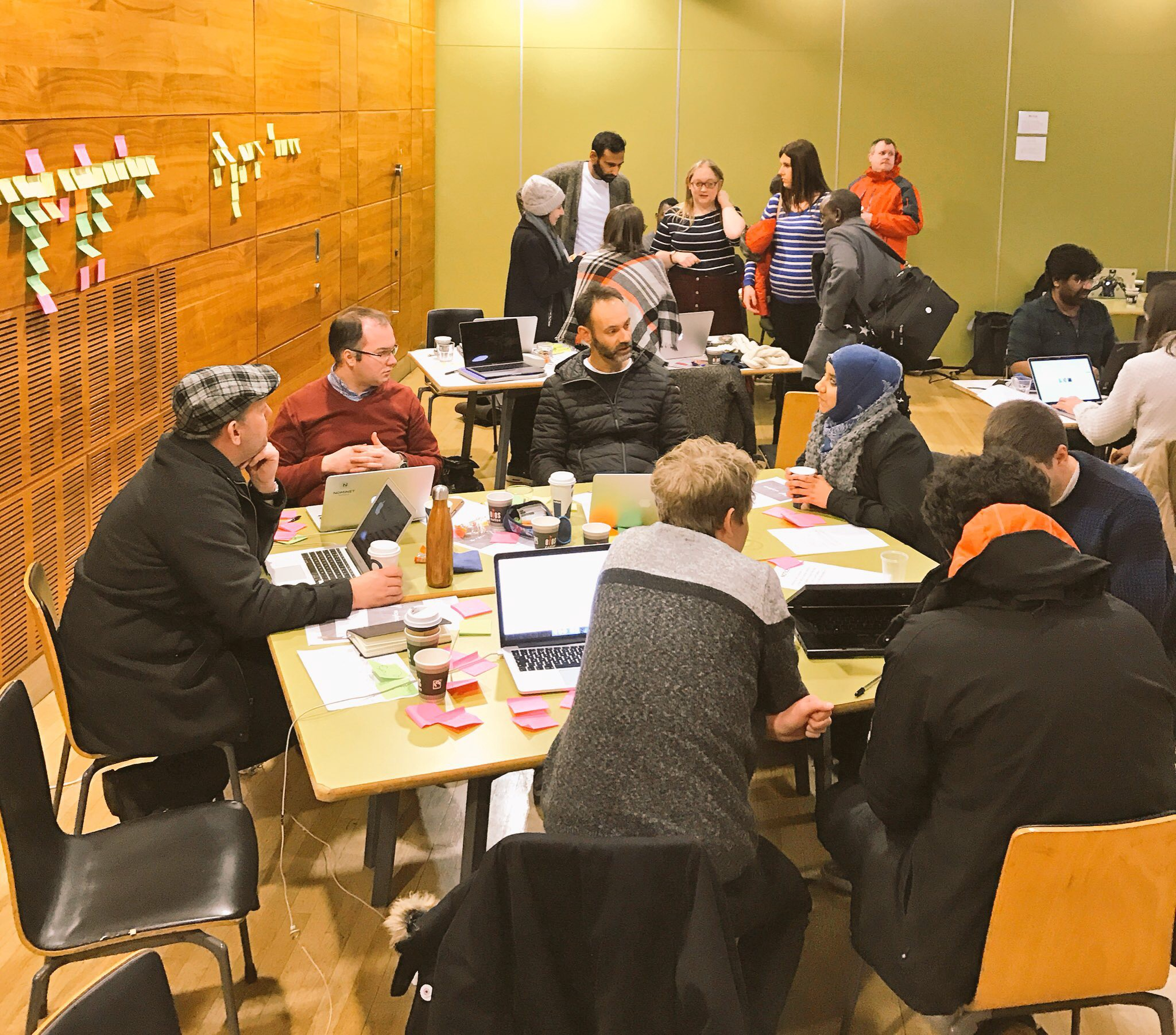 Room full of people — about 3 table groups of people chatting