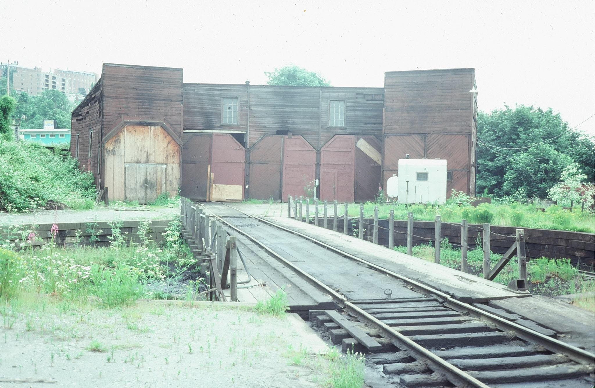 An image of the boarded up roundhouse with turntable in the foreground