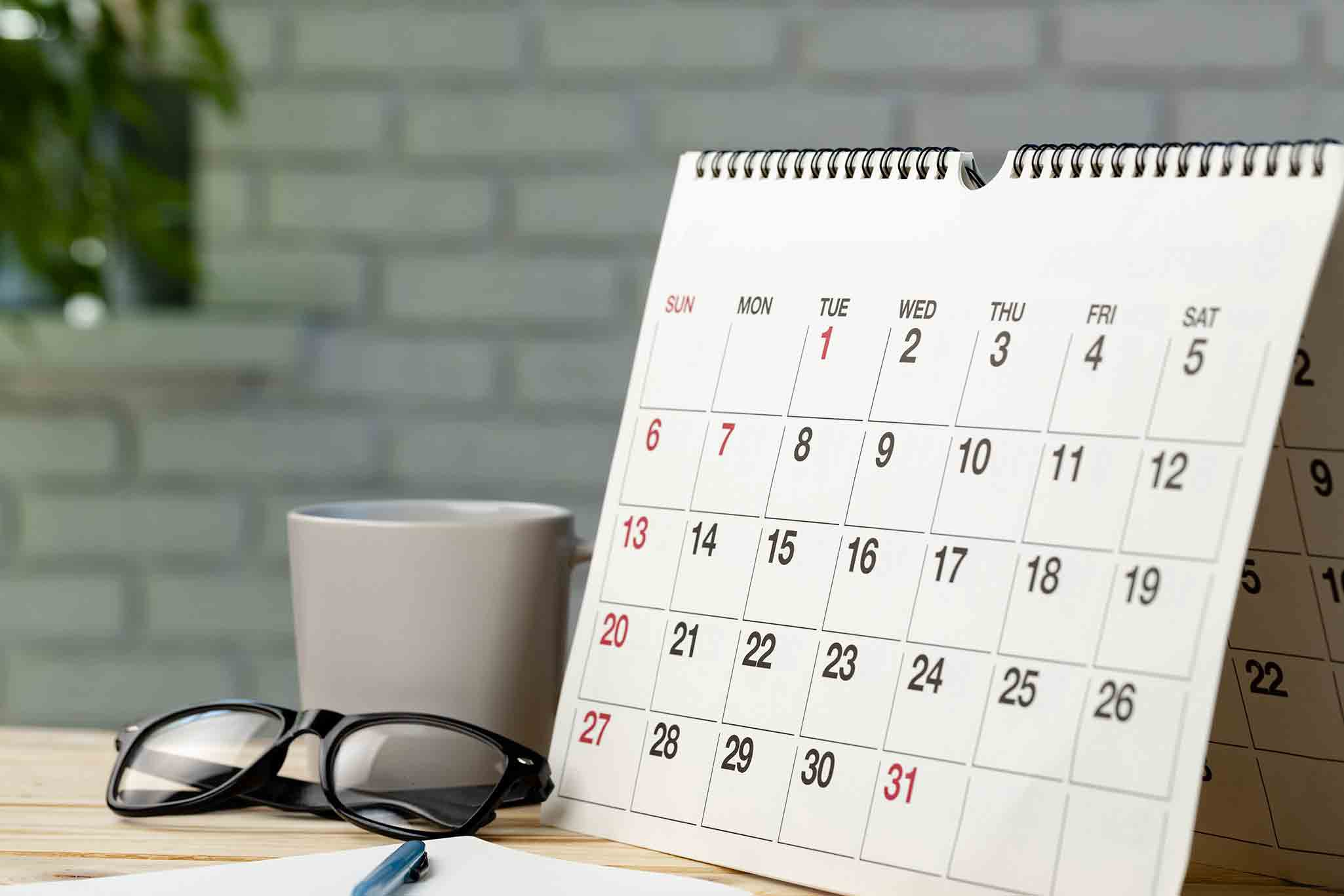 Unmarked calendar propped up on a desk, next to pen, paper, glasses and coffee mug.