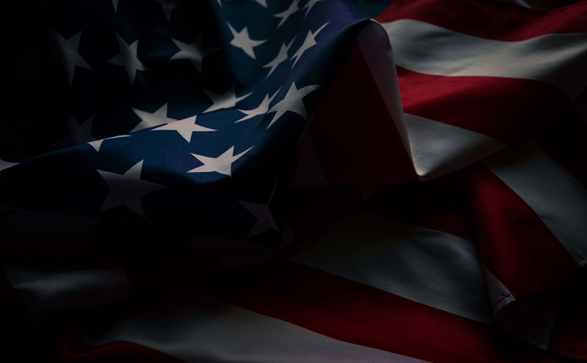 Close-up of the American flag with a dark filtered background.