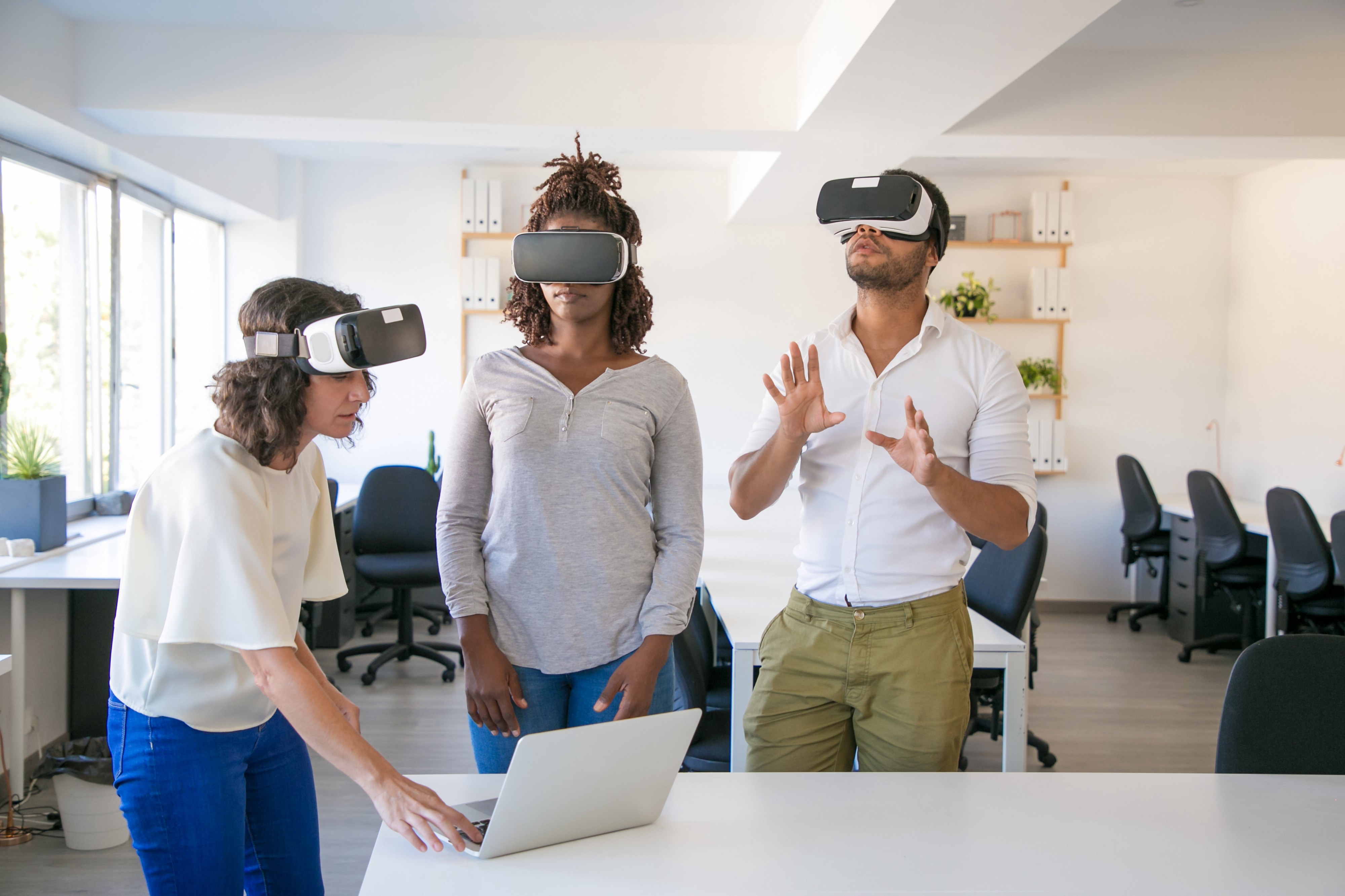 Three people using Virtual Reality holographic headsets, twin technology of Augmented Reality, wich can increase e-commerce sales without the need of such special equipaments.