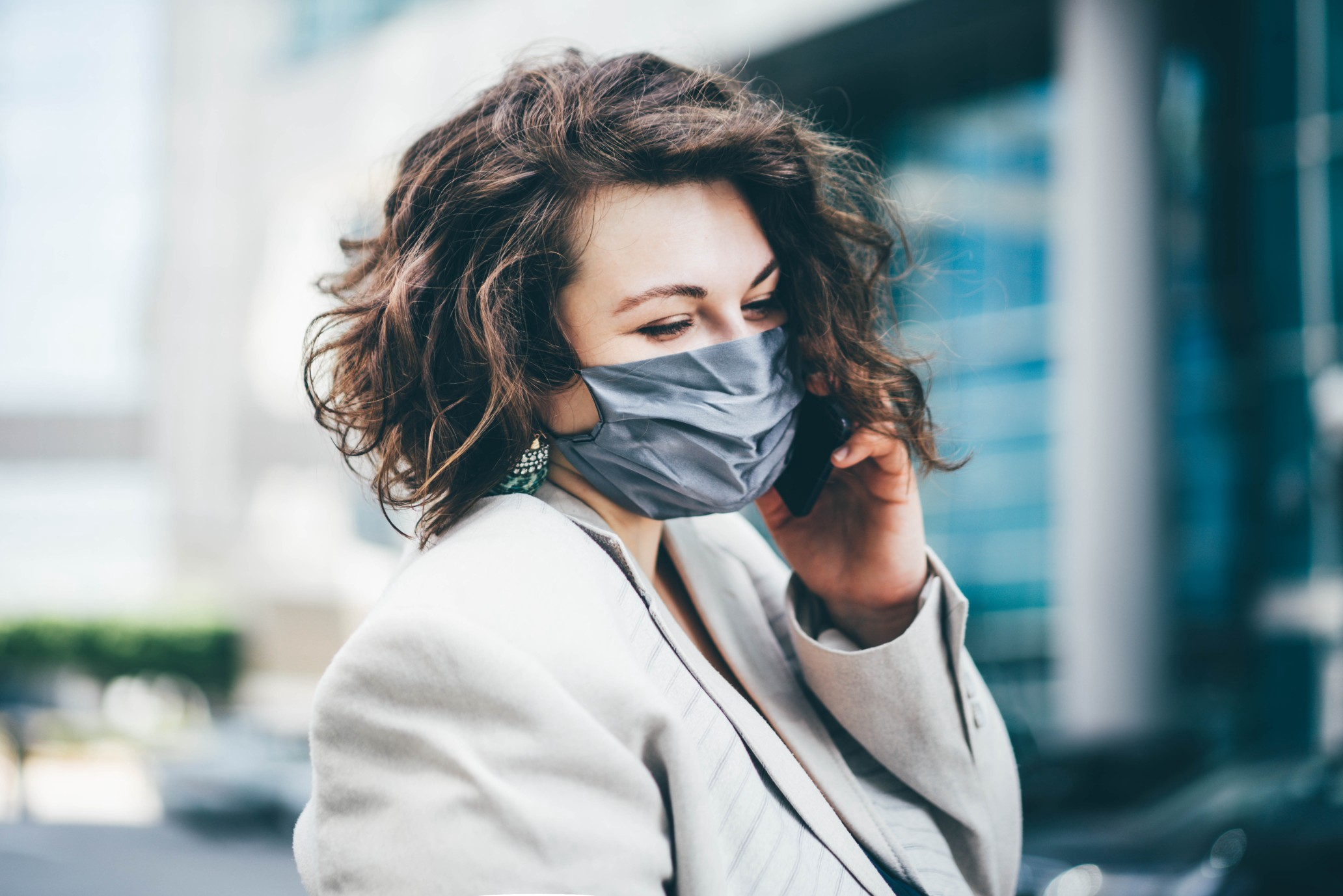 A stylish woman with short brown hair smiles behind a mask in the city.