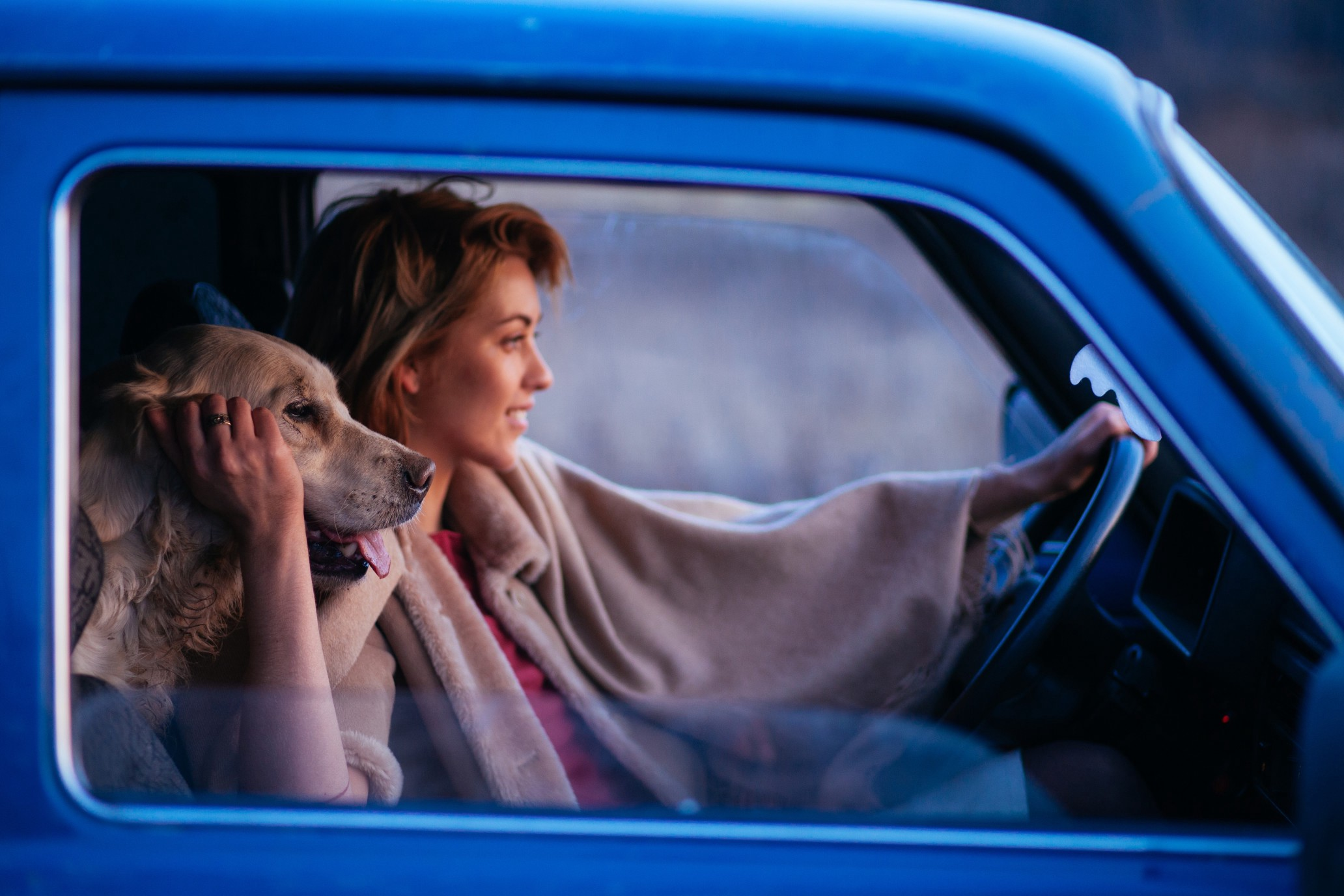 A woman in a blue truck smiles as she holds her steering wheel and pets her dog, whose head rests on her shoulder.