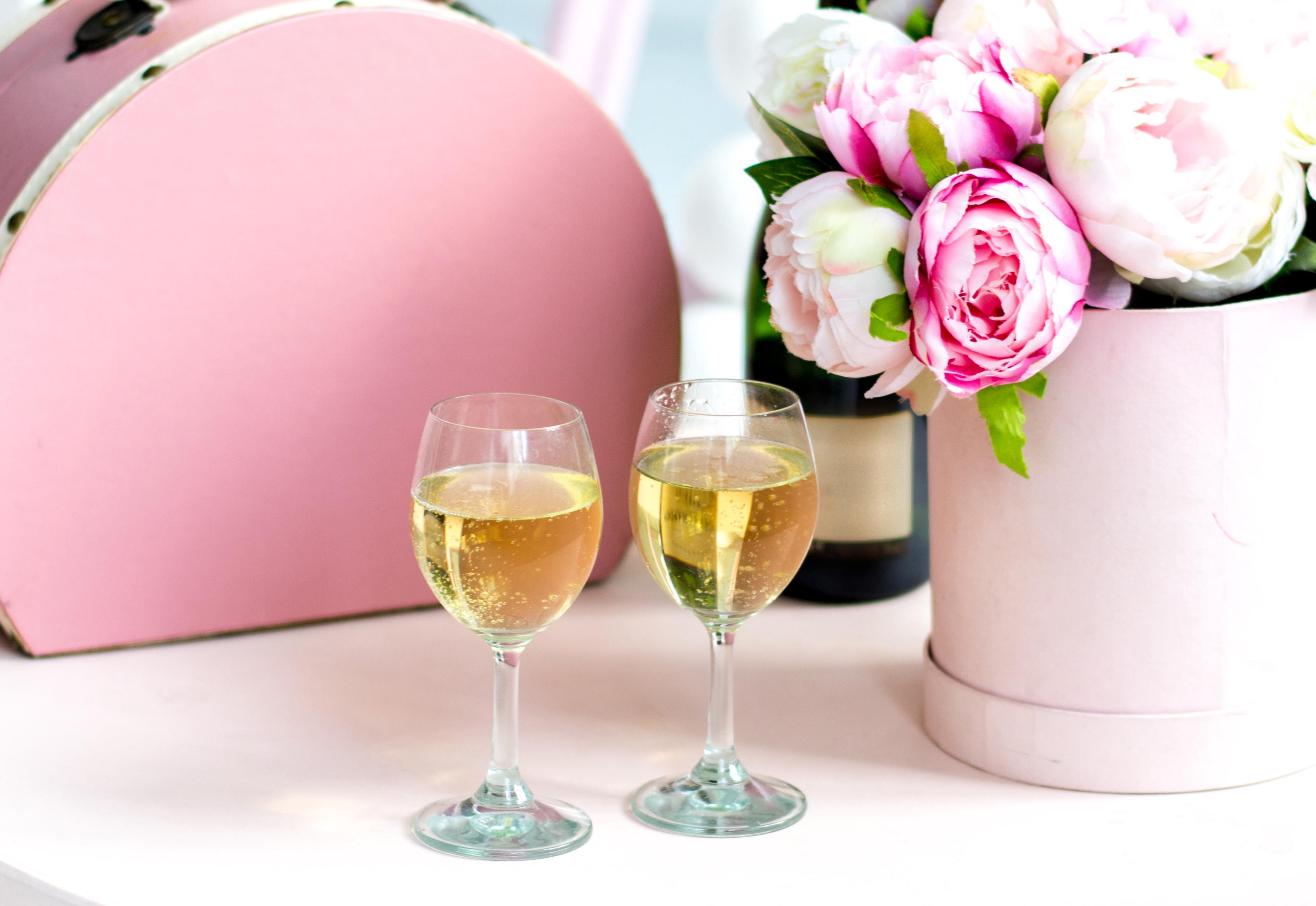 Two glasses of sparkling wine sit next to a bouquet of pink and white roses.
