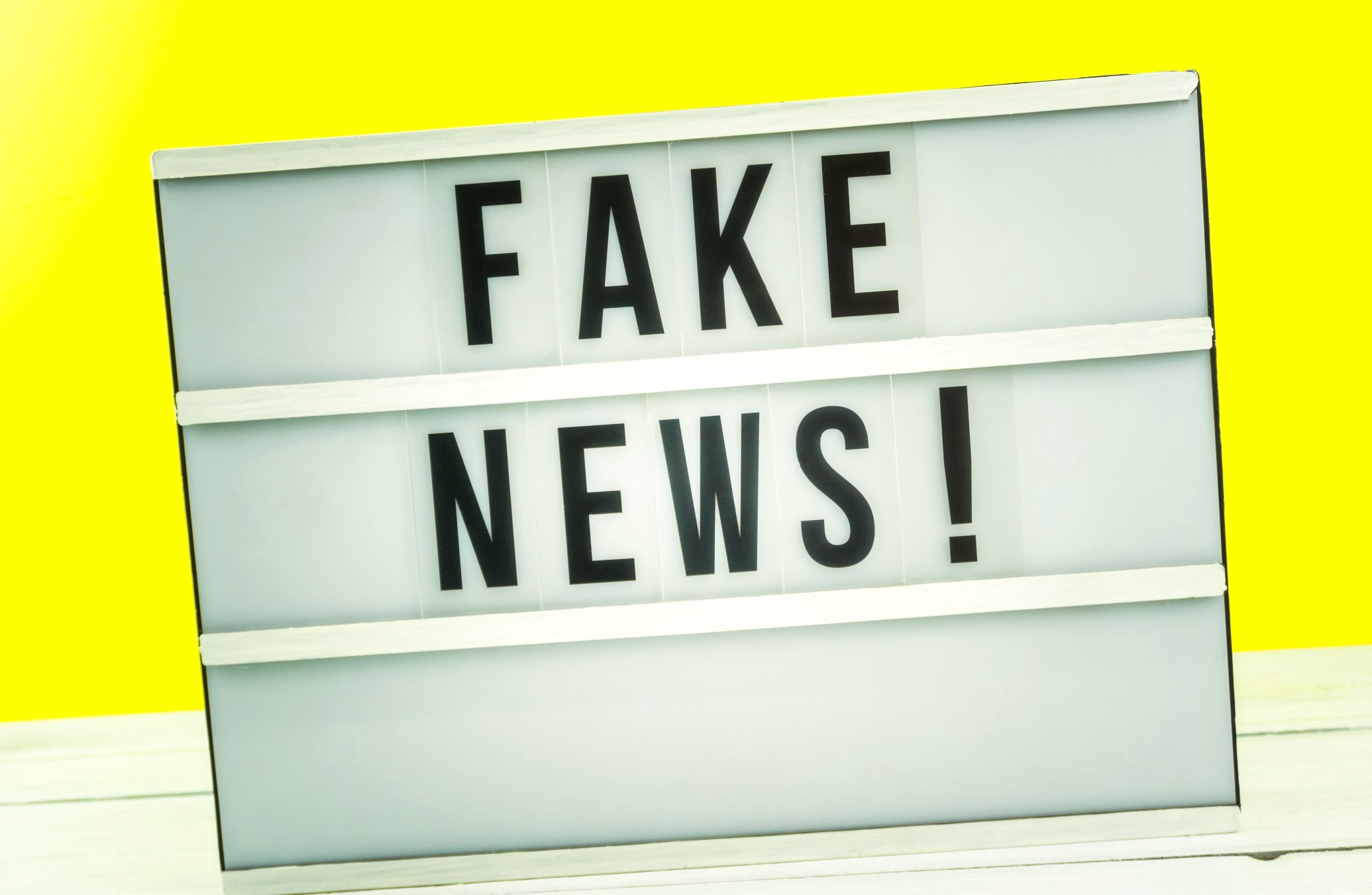 "A ""fake news"" sign sits against a wall of yellow."
