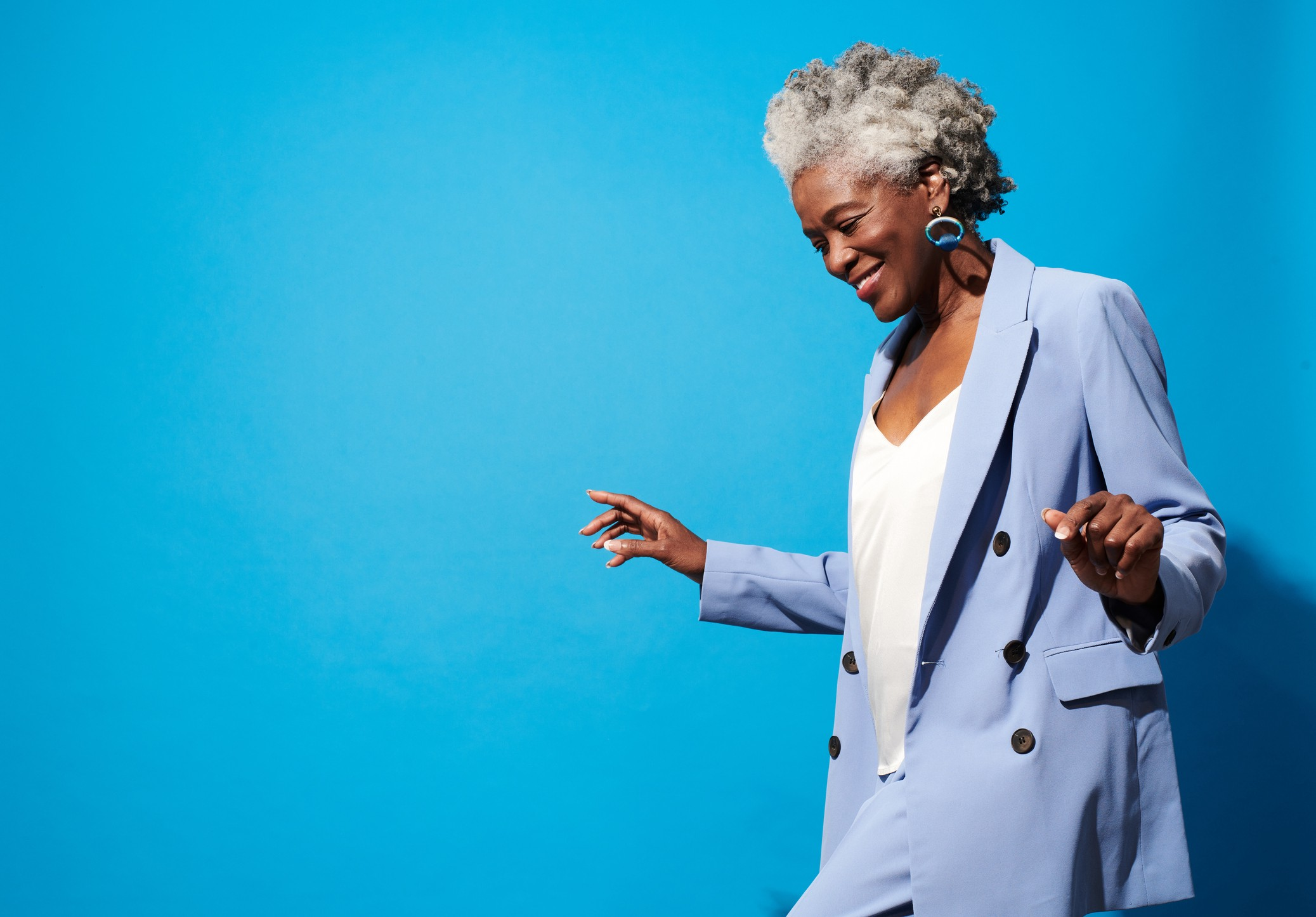 Confident, smiling older Black woman in a powder blue suit against a sky blue background.