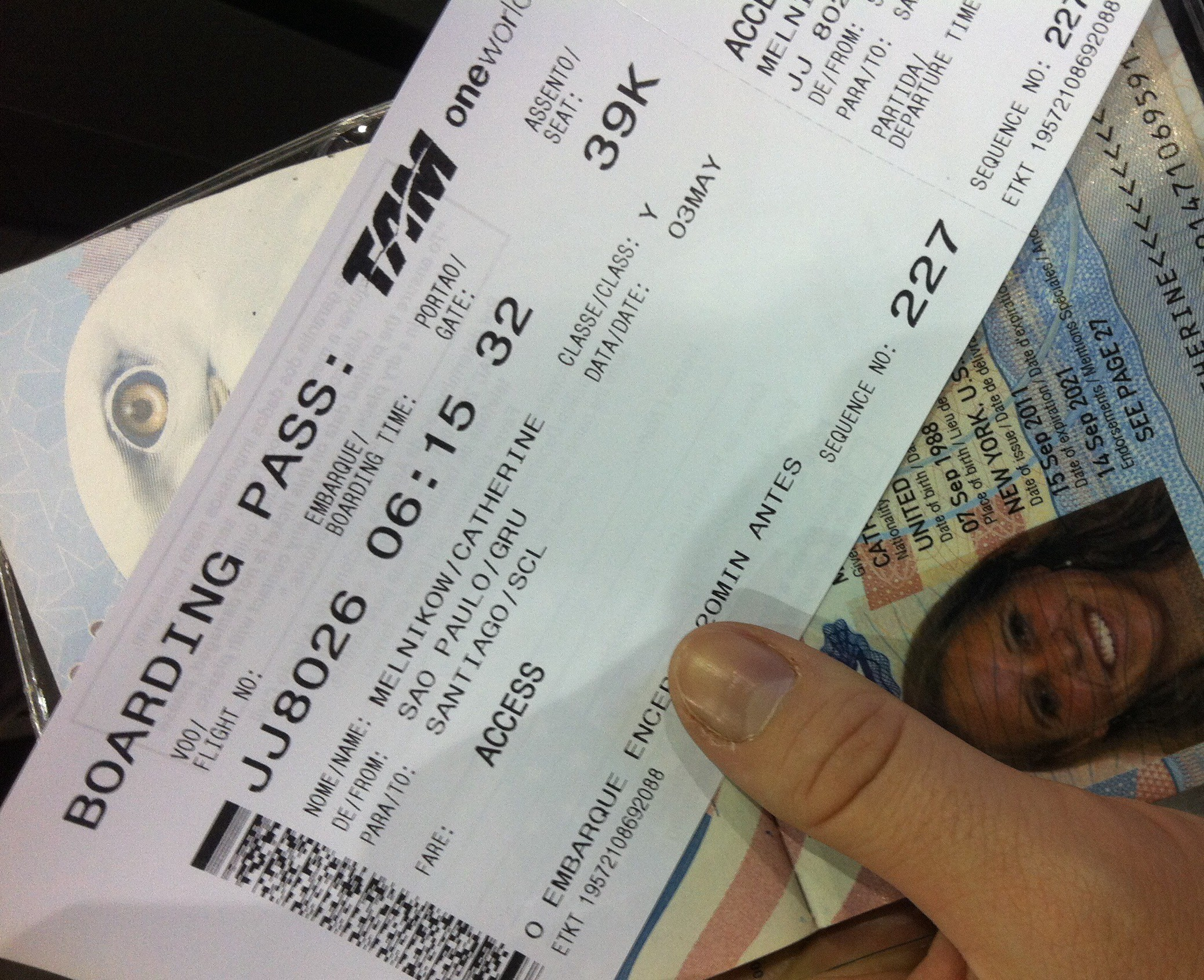 A ticket and passport held in hand
