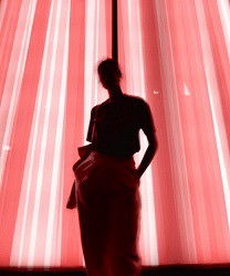 Portrait silhouette of a woman standing in front of an illuminated pink curtain