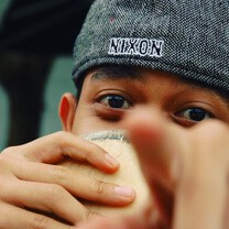 A young man in a cap points at the screen, his mouth obscured by a coffee cup.