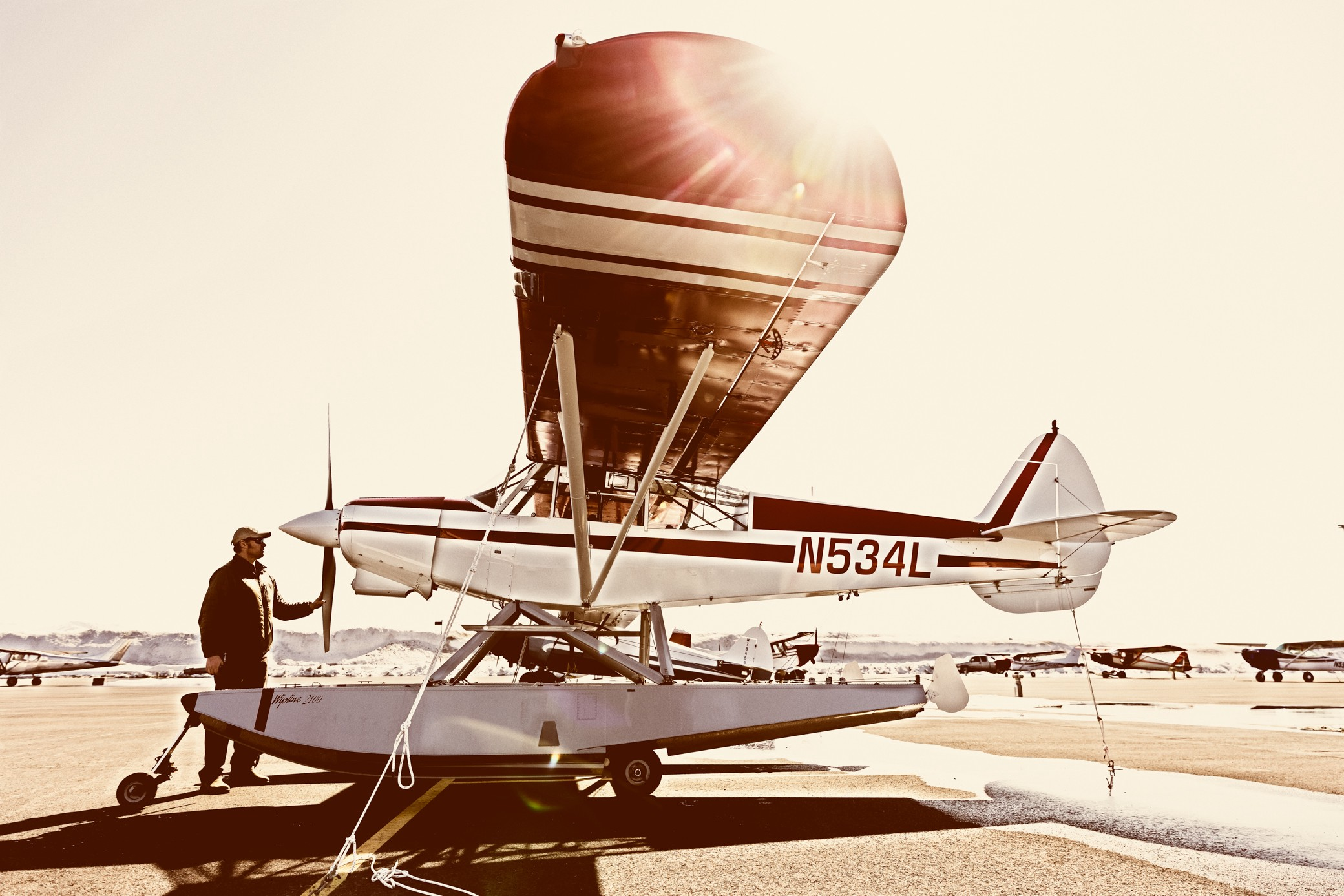man in front of a float plane on a sunny day