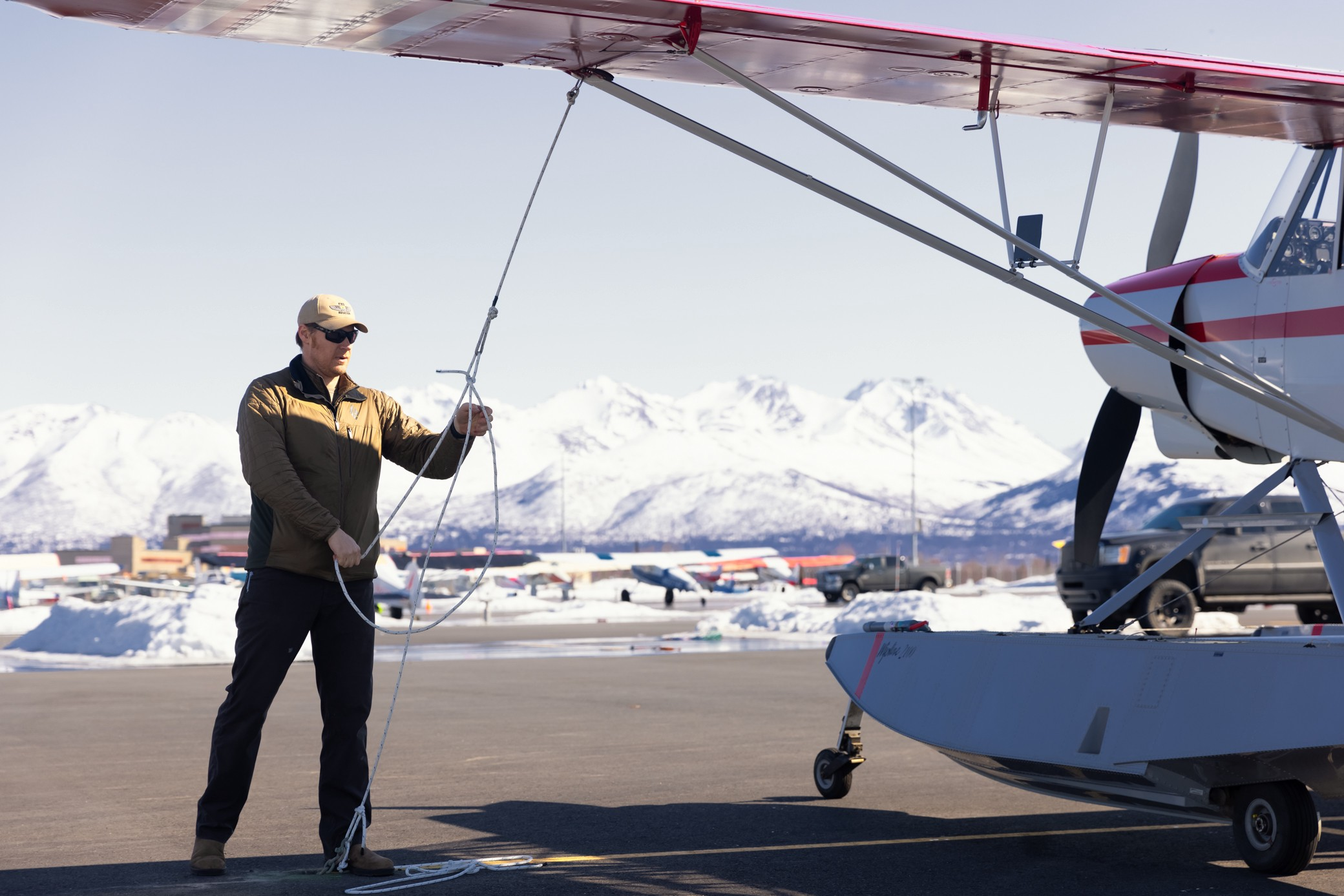 Man outside of a float plane with mountains in the background
