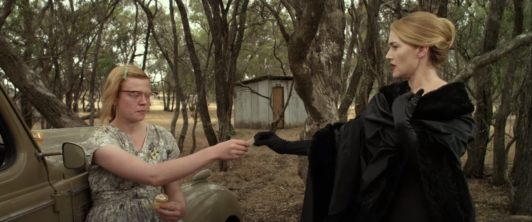 A screencap from The Dressmaker, showing Tilly in haute couture handing her calling card to the plainly-dressed Gertrude.