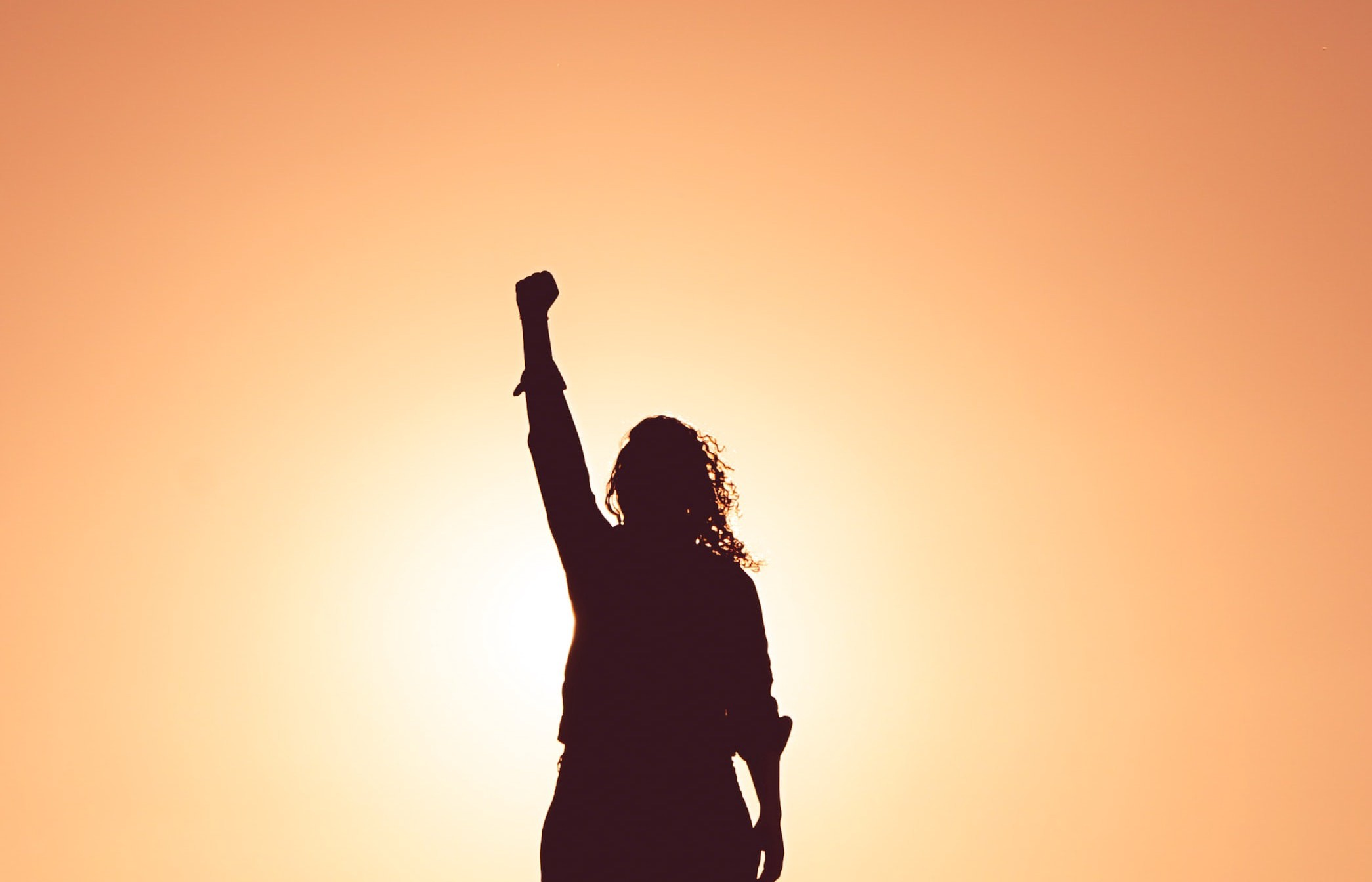 Silhouette of a person that may be a woman with raised right fist in front of yellow/orange light similar to sunrise/sunset/