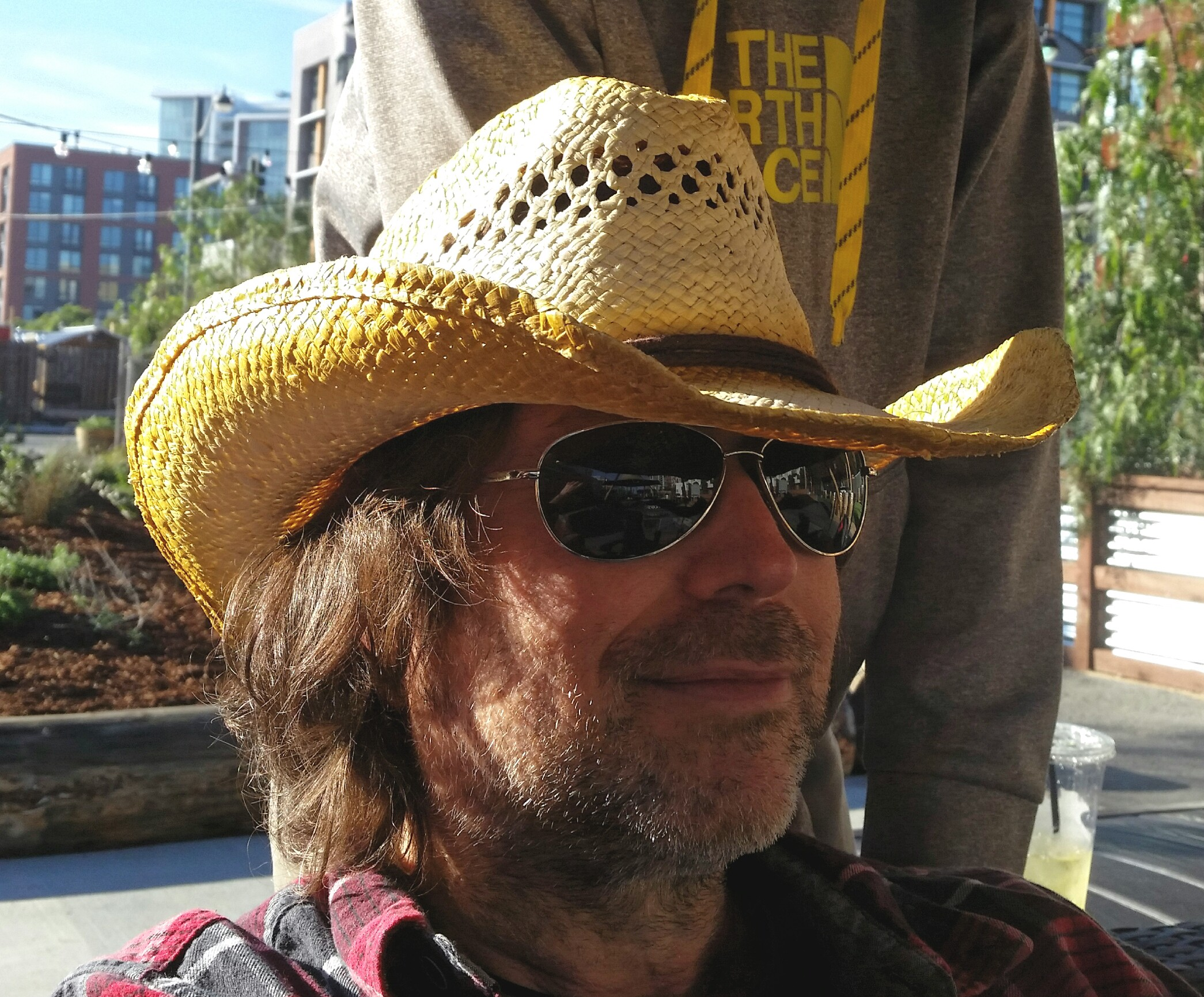 Man wearing a cowboy hat and sunglasses.
